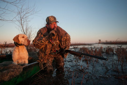 A duck hunter and his dog watching a flock of ducks nearby.