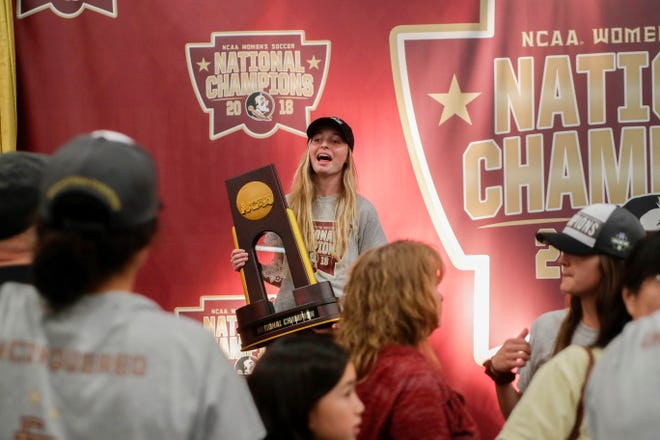 Florida State defender Gabby Carle poses with the national championship trophy during a ceremony honoring the team in the Champions Club West at Doak Campbell Stadium Monday, Dec. 3, 2018.