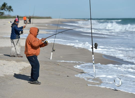 Vero Beach residents Salvador Lambin (front) and Eric Medina spend the cold morning bundled up fishing from the shore of South Beach Park as temperatures that dipped into the low 40s from a cold front begin to rise on Wednesday, Nov. 28, 2018, in Vero Beach.