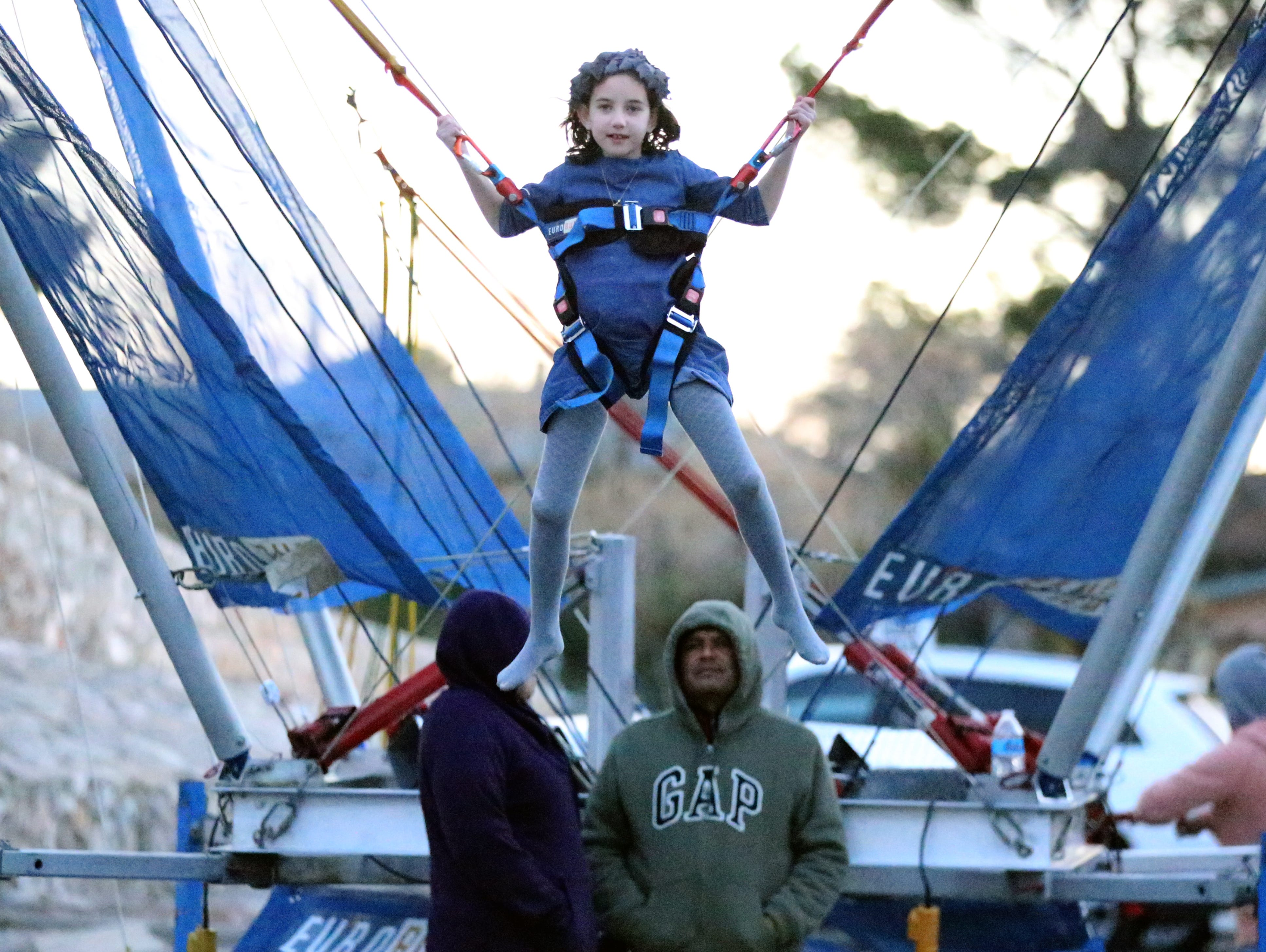 Musia Greenberg, 7, jumps while on a harness on an outdoor attraction at the Chabad Lubavitch Chanukah Playground Sunday.