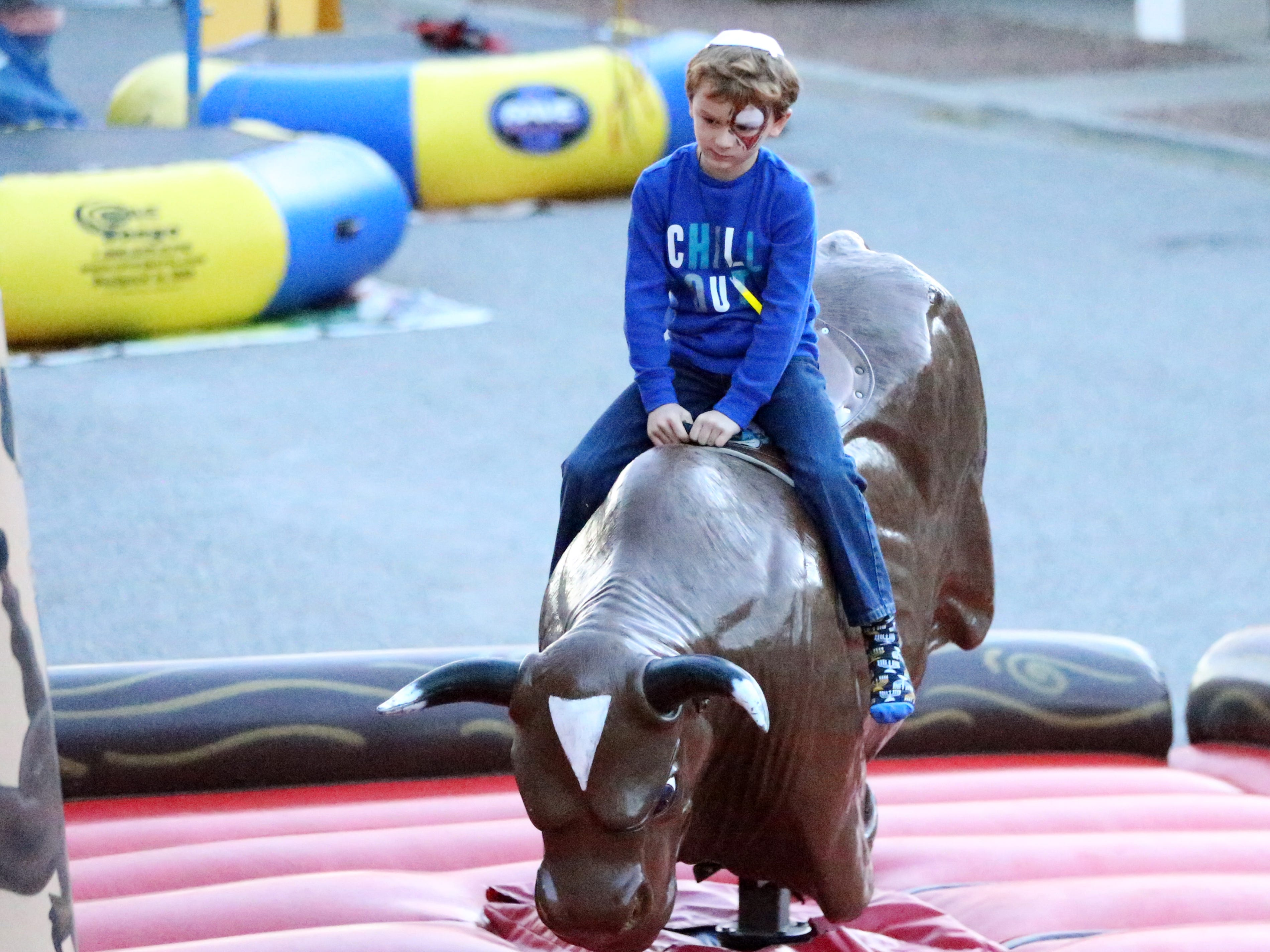 Brodie Kupetz, 6, rides a moving bull attraction Sunday at the Chanukah Playland.