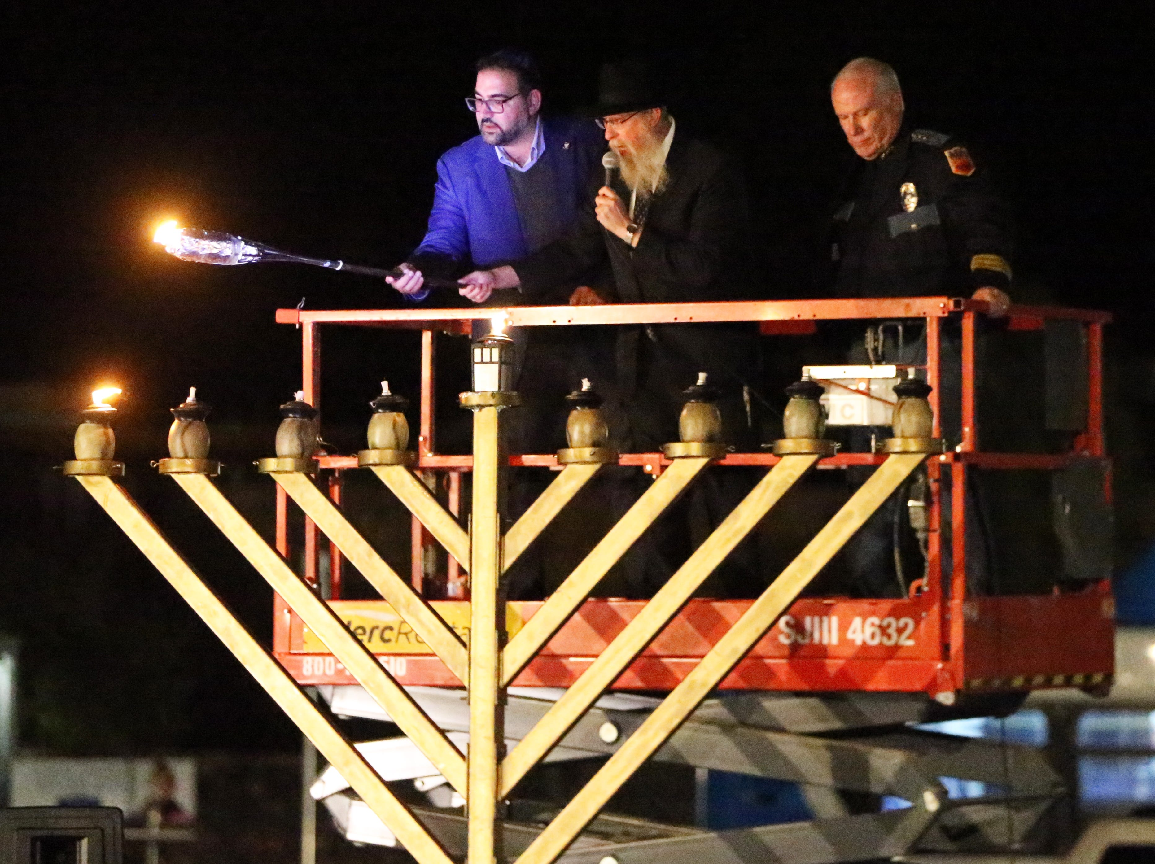 Rabbi Yisroel Greenberg, center, of Chabad Lubavitch of El Paso at 6615 Westwind Drive leads the lighting of a large menorah with city Rep. Peter Svarzbein, left, and assistant chief of police Peter Pacillas Sunday outside the synagogue in West El Paso. The event marked the beginning of Chanukah with the lighting of the first candle on the menorah. Seven more will be lit on subsequent nights. The Jewish holiday commemorates the rededication of the Holy Temple in Jerusalem following the defeat of the Syrian-Greek army in the second Century BCE. While planning to light the Temple menorah they had only a small supply of pure olive oil to use as fuel, but the small supply miraculously lasted all eight nights. Chabad Lubavitch also held a Chanukah Playland and the lighting of a 'Toynorah' for children before the Menorah lighting.