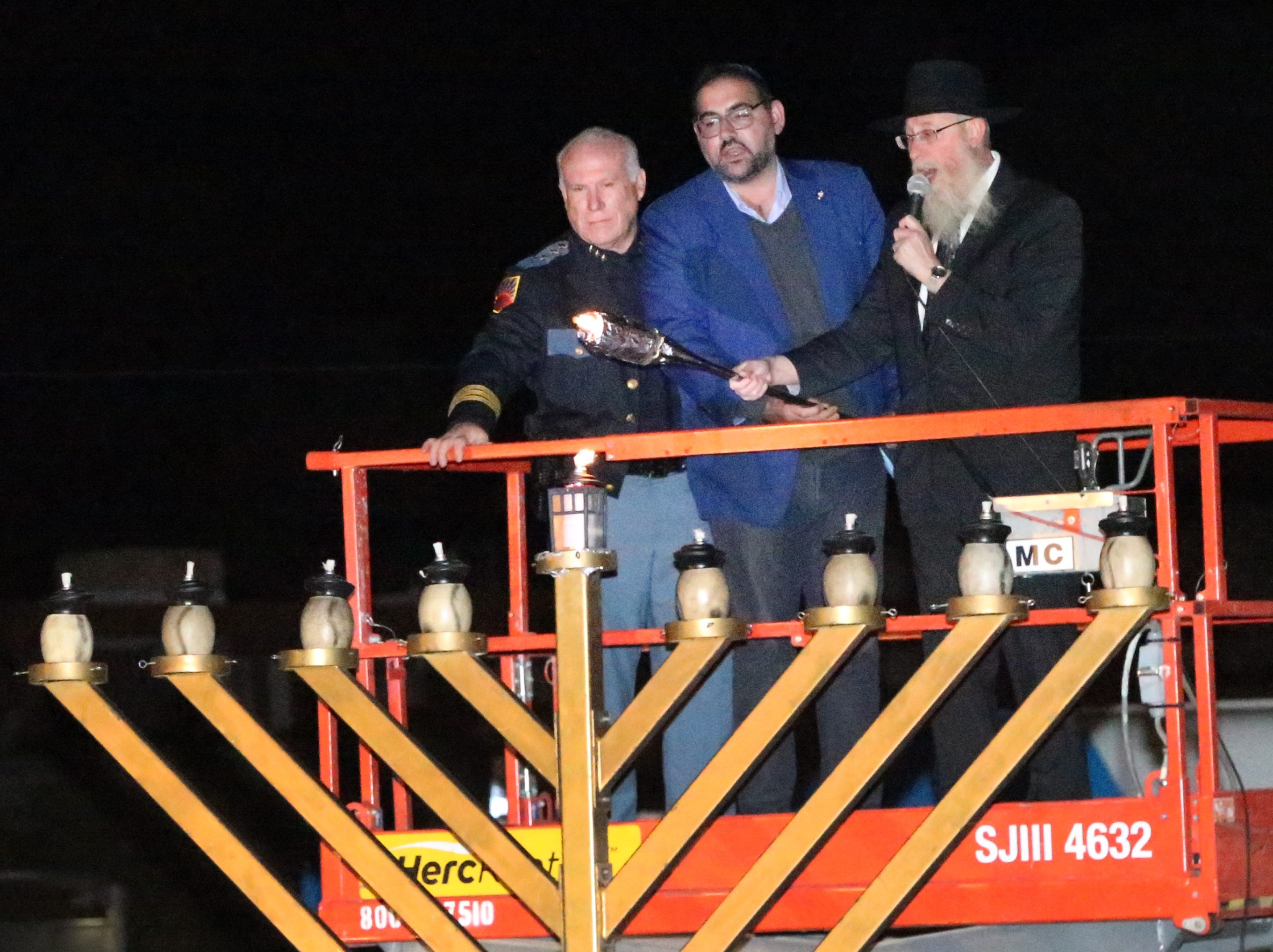 Rabbi Yisroel Greenberg, right, lights the center candle of a large menorah with help from El Paso police assistant chief Peter Pacillas, left, and Westside city Rep. Peter Svarzbein, center, Sunday night to commemorate the start of Chanukah observance.