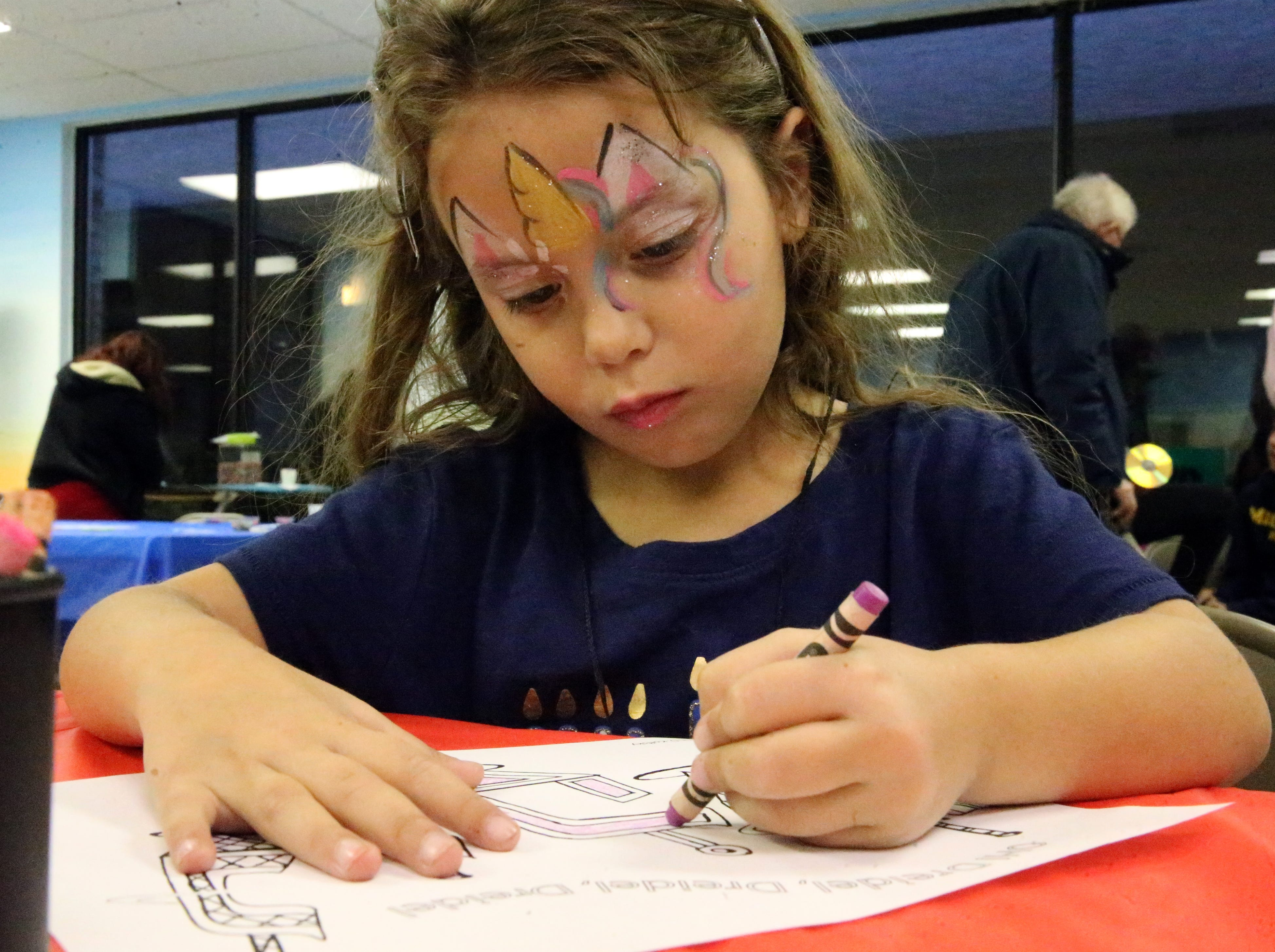 Esther Ribault, 5, of El Paso colors a page of traditional Jewish Dreidels at the Chabad Lubavitch Chanukah Playland Sunday night.