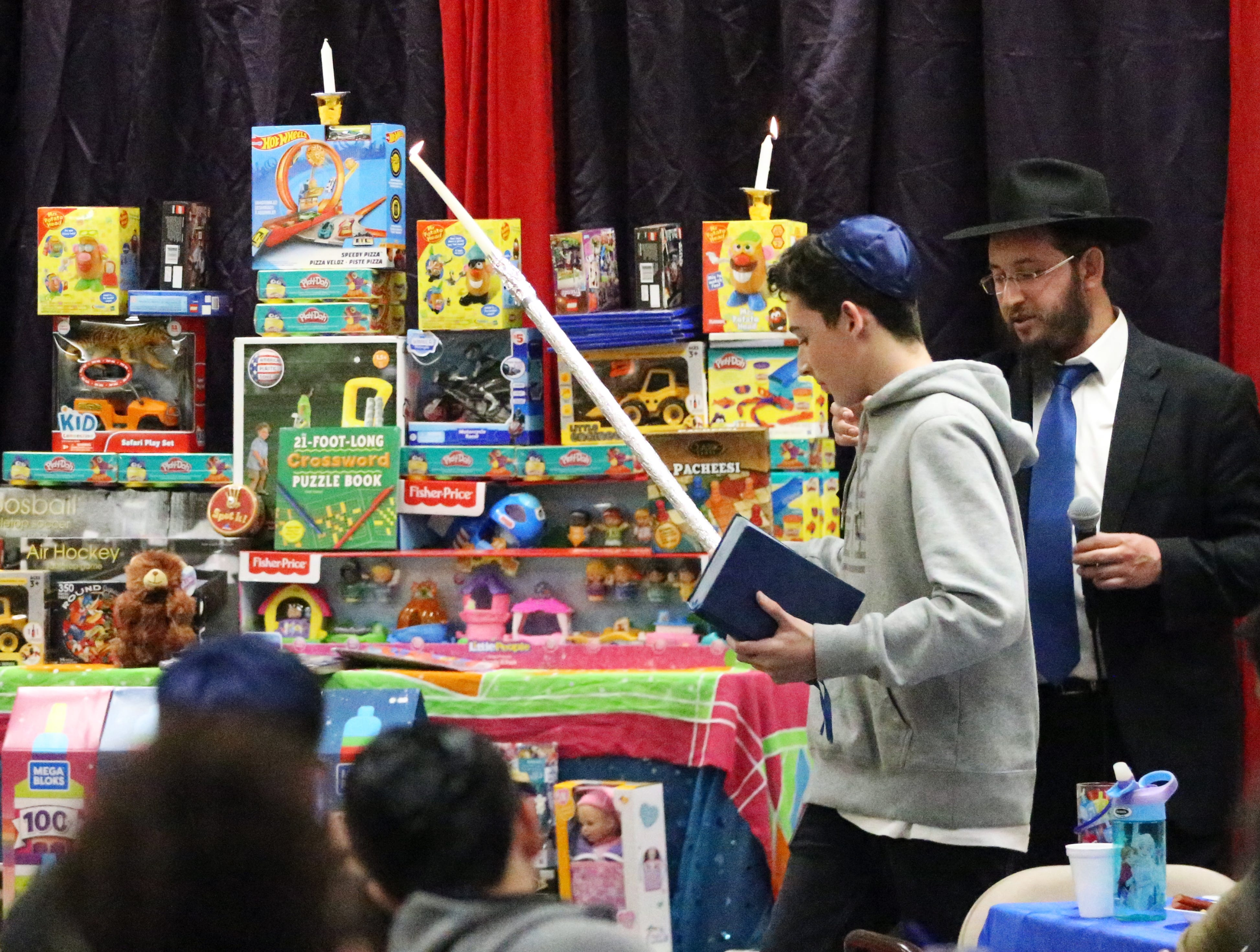 Rabbi Levi Greenberg of Chabad Lubavitch helps light a 'toynorah' made of donated toys to be given to children at area hospitals.