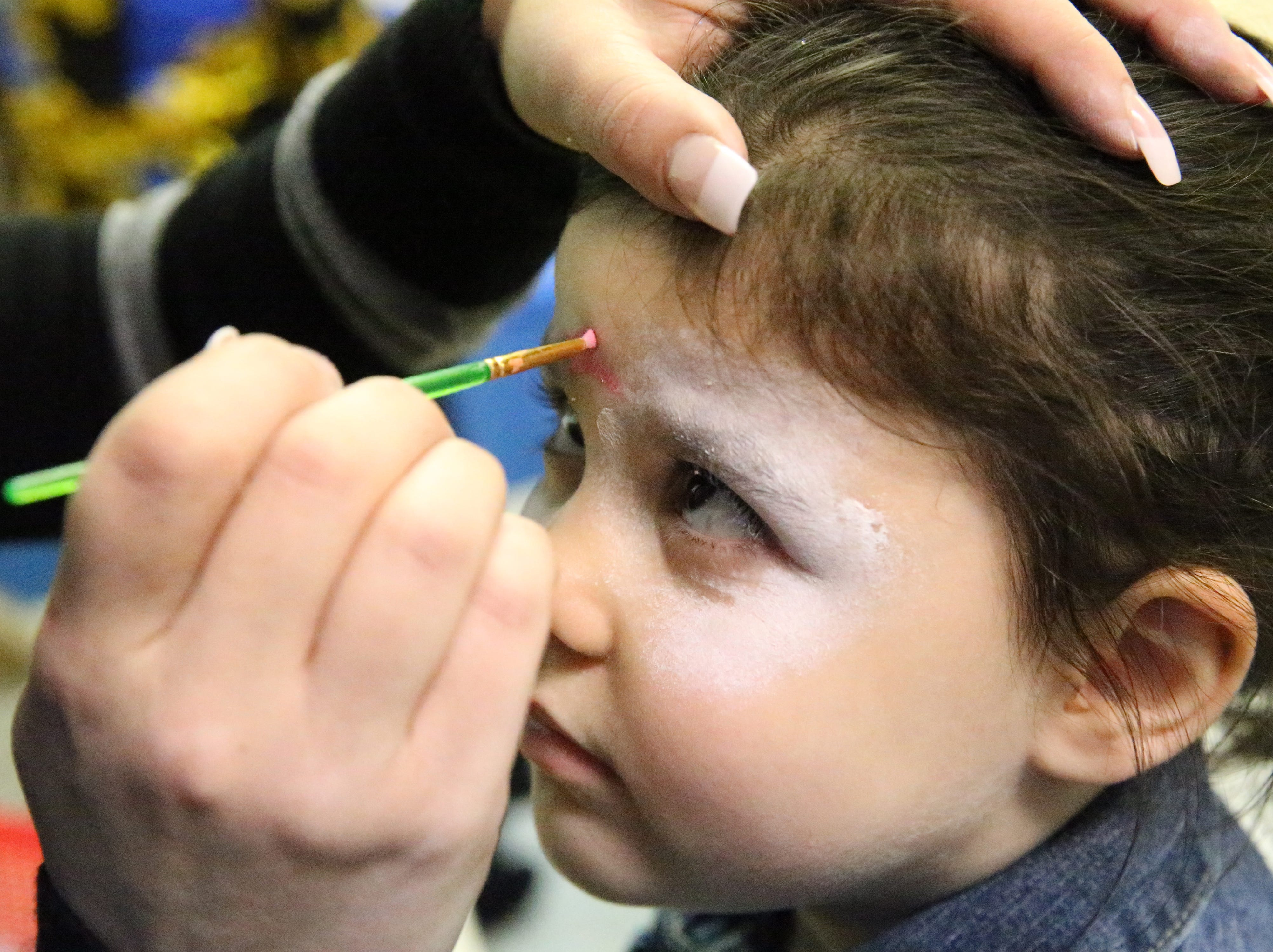 Kali Keating, 3, gets her face painted at the Chanukah Playland Sunday at Chabad Lubavitch, 6615 Westwind Drive.