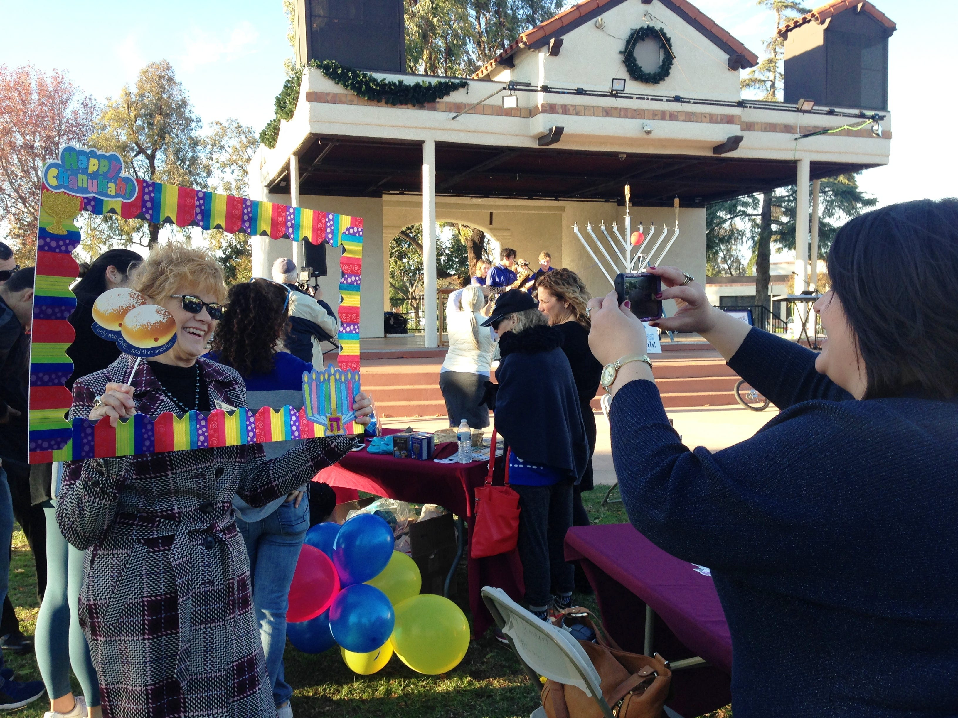 Nancy Lee Phillips, representing Ventura County Supervisor Kelly Long, poses for a photo being taken by Elina Hirman on Sunday at Chabad of Camarillo's 16th annual Hanukkah Festival and Grand Menorah Lighting in Constitution Park in Camarillo.
