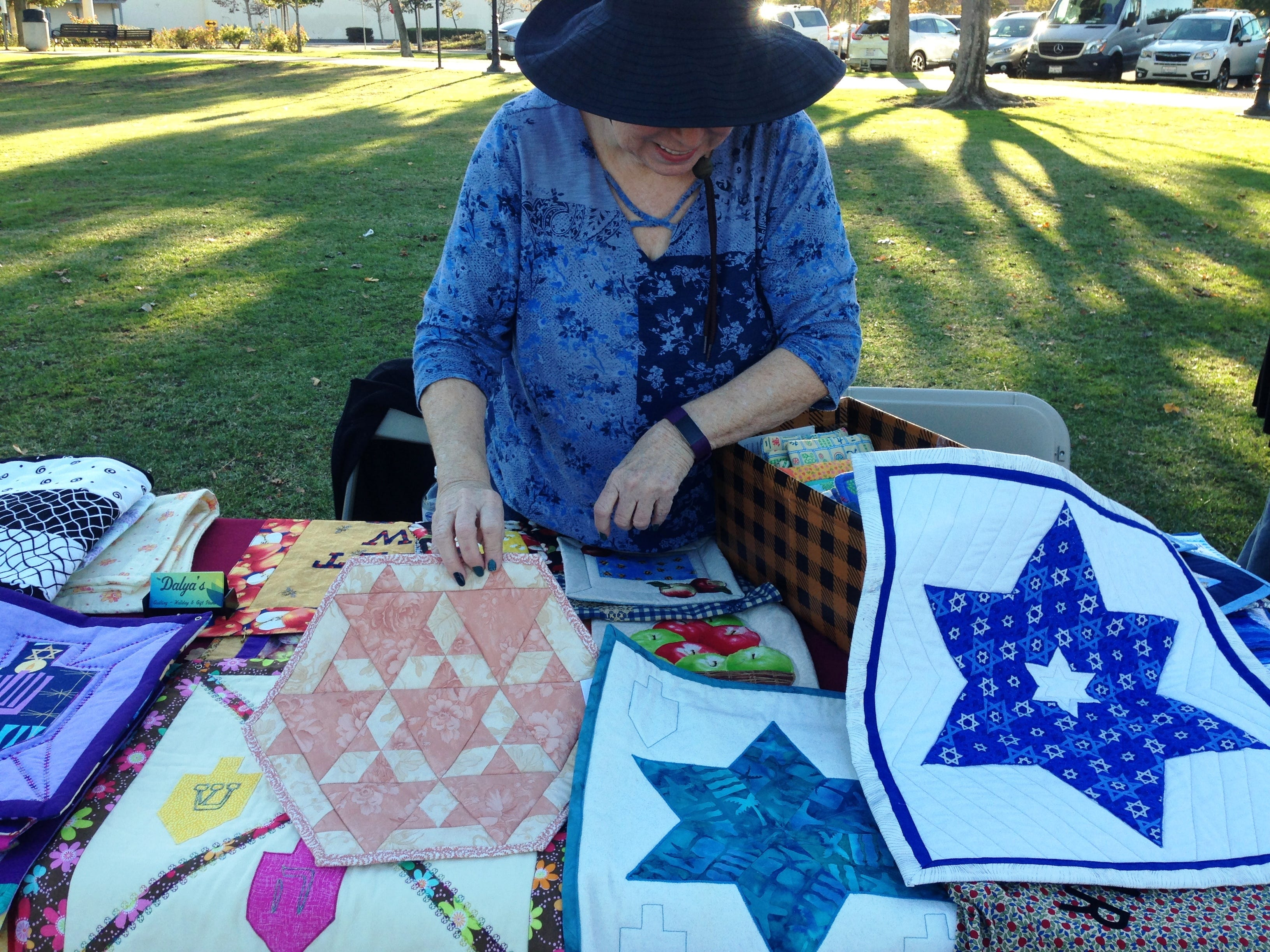 Dalya Dektor displays her handmade quilts on Sunday at Chabad of Camarillo's 16th annual Hanukkah Festival and Grand Menorah Lighting in Constitution Park in Camarillo.