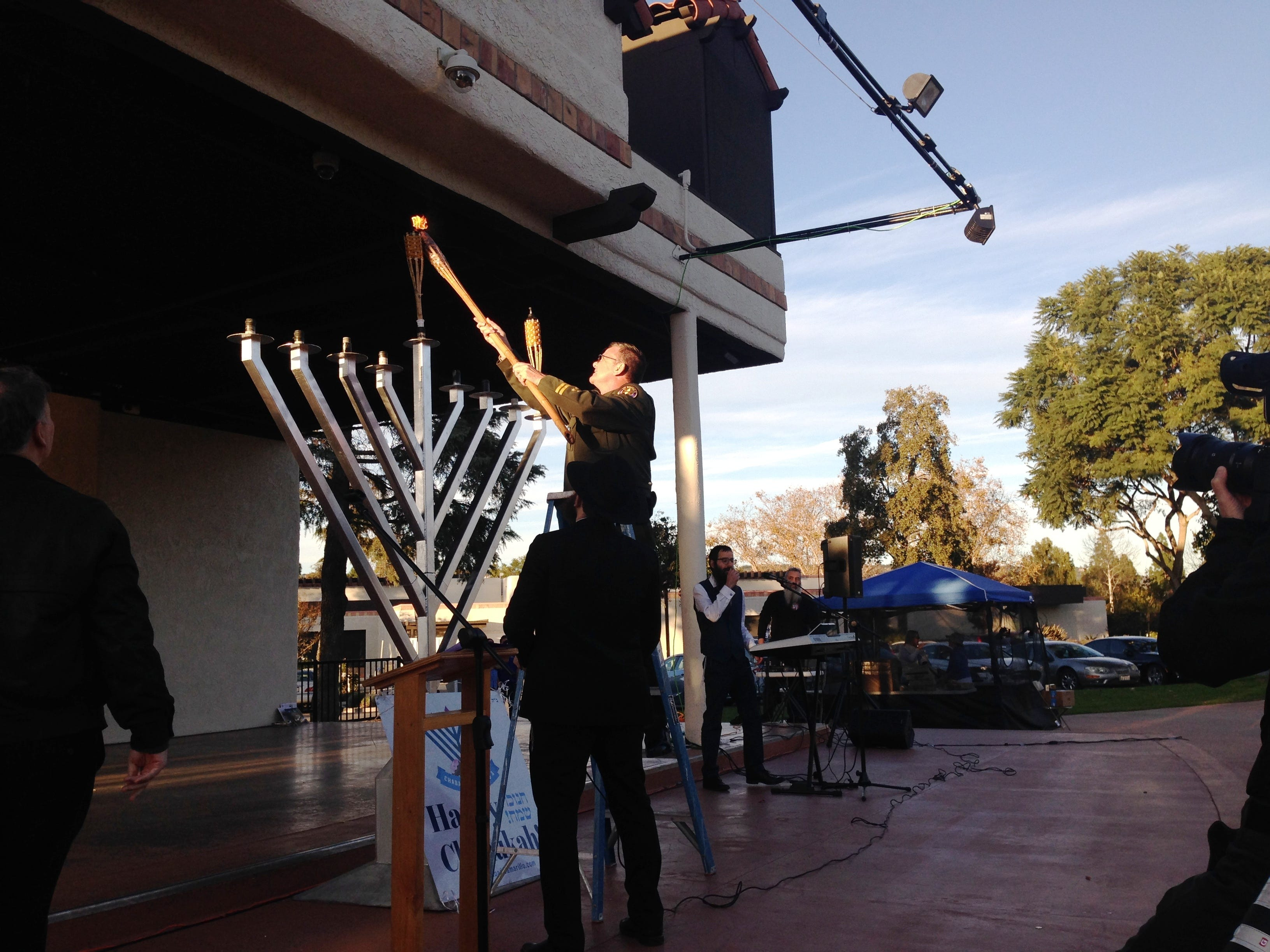 Ventura County Assistant Sheriff Chris Dunn lights a candle on Sunday at Chabad of Camarillo's 16th annual Hanukkah Festival and Grand Menorah Lighting in Constitution Park in Camarillo.
