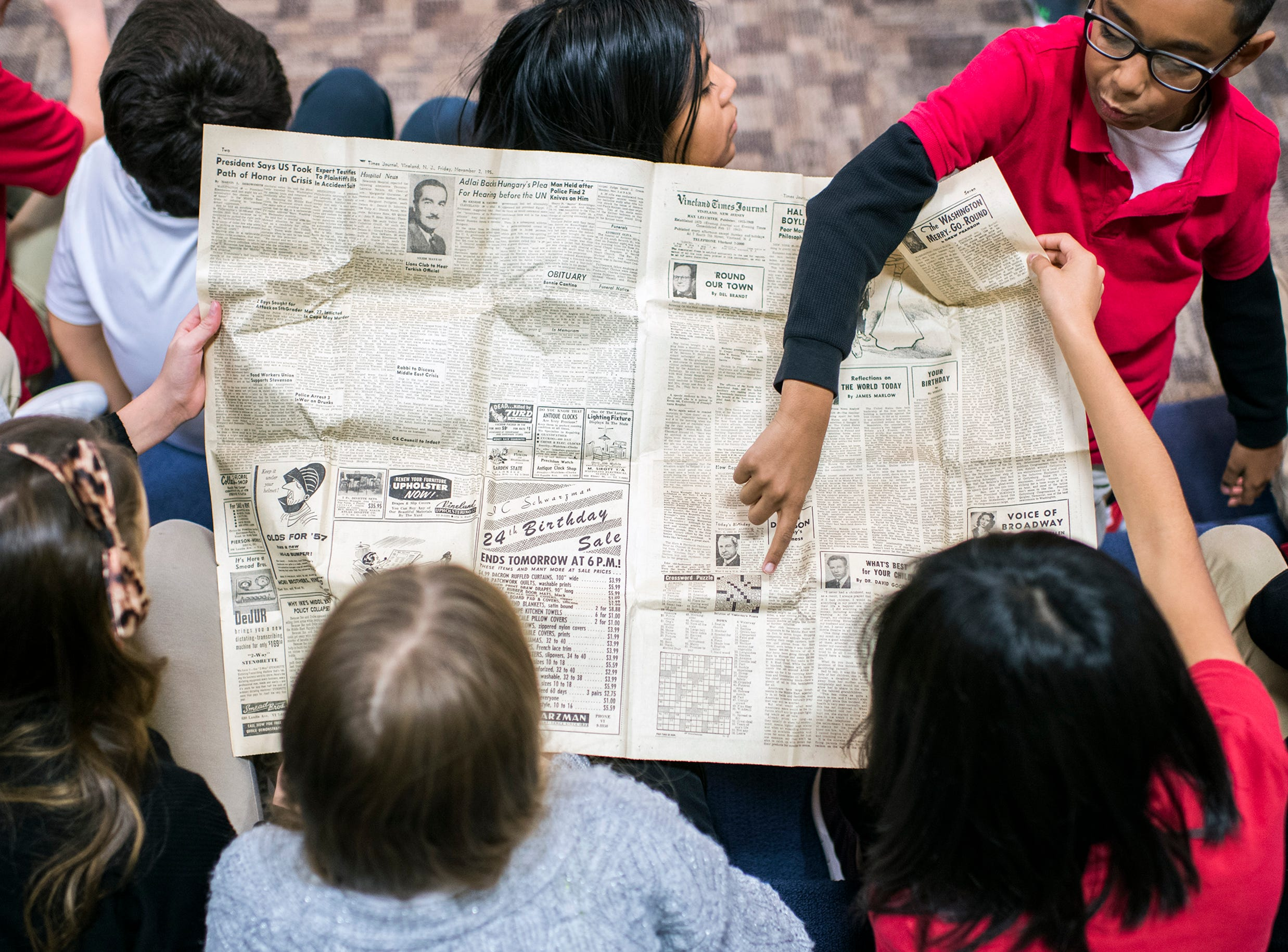 Students look over an old newspaper after a time capsule from 1956 was opened at Marie Durand Elementary School Monday, Dec. 3, 2018 in Vineland, N.J.