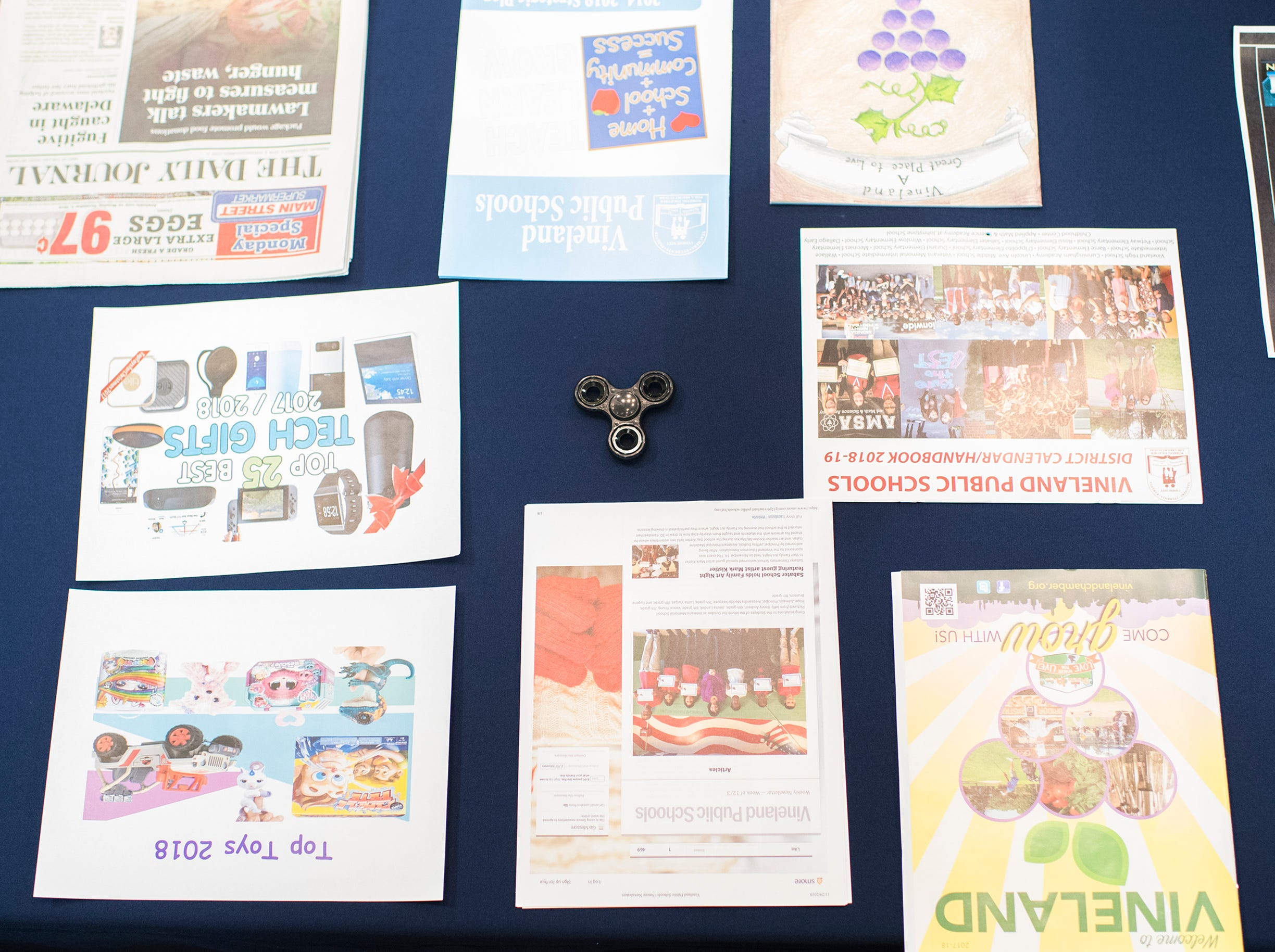 Modern additions, including a fidget spinner, are added to a time capsule from 1956 at Marie Durand Elementary School Monday, Dec. 3, 2018 in Vineland, N.J.