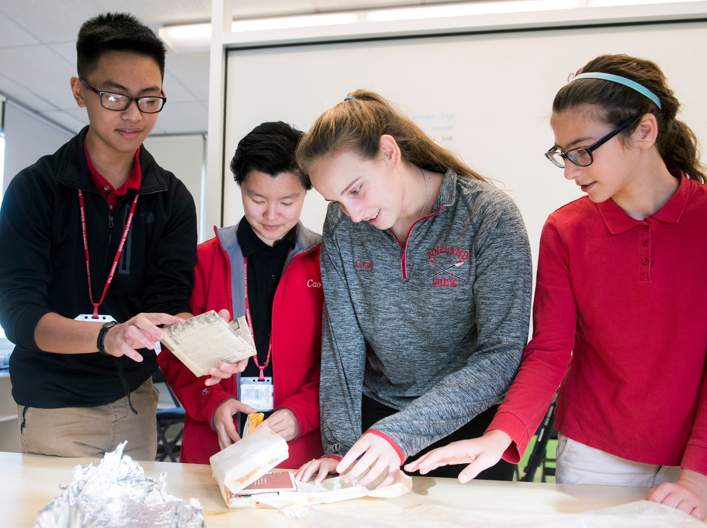 Students Rodrick-Josh Zapata, 15, Amanda Cao, 16, Faviana Cohen, 16, and Sarah Hullihen open the contents of a time capsule dating back to 1957 Monday, Dec. 3, 2018 at Johnstone Elementary School in Vineland, N.J.