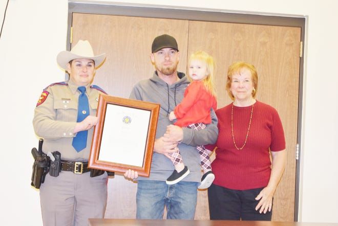 DPS Trooper Rachel Russell stands with Brian Young and his daughter, and Diana Winslow after Young was recognized for his heroic actions in pulling Winslow out of her vehicle after it was involved in a crash near his home.