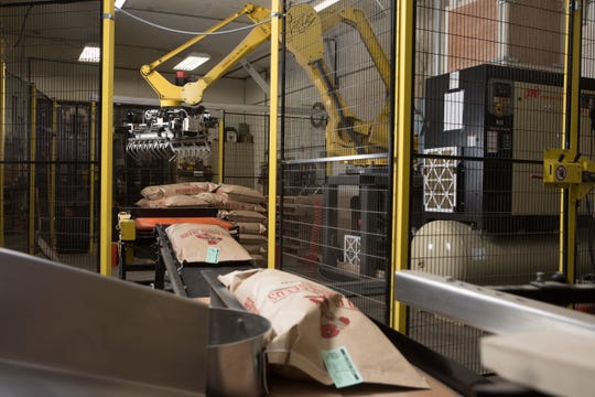 """A robotic stacking arm, named """"Lester,"""" stacks seed oats onto pallet at Schumitsch Seed Inc."""