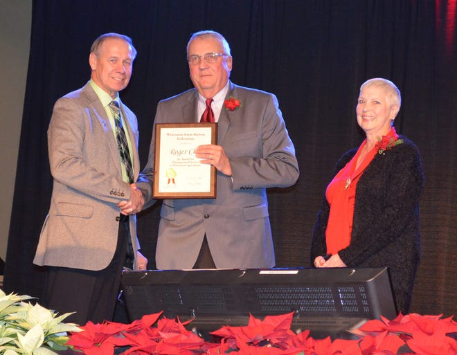 Wisconsin Farm Bureau President Jim Holte (left) presents Roger Cliff and wife, Cathy, with the Distinguished Service to Agriculture Award.