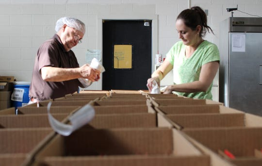 Employees pack baking mix into boxes at Foodworks Alliance.