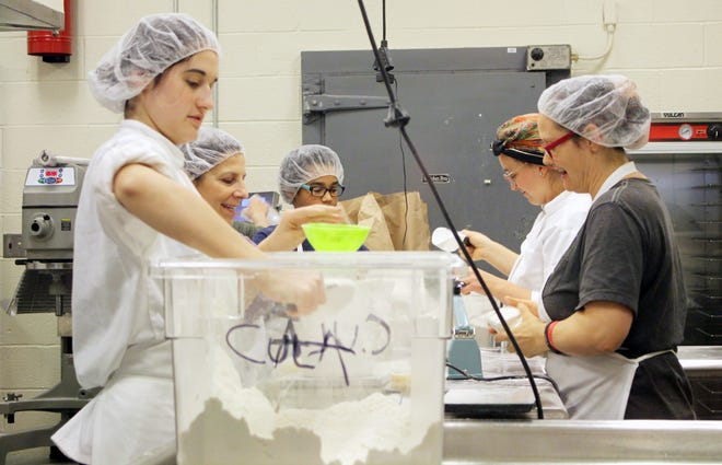 Employees prepare packages of Bella Gluten Free baking mix in the Foodworks Alliance kitchen.