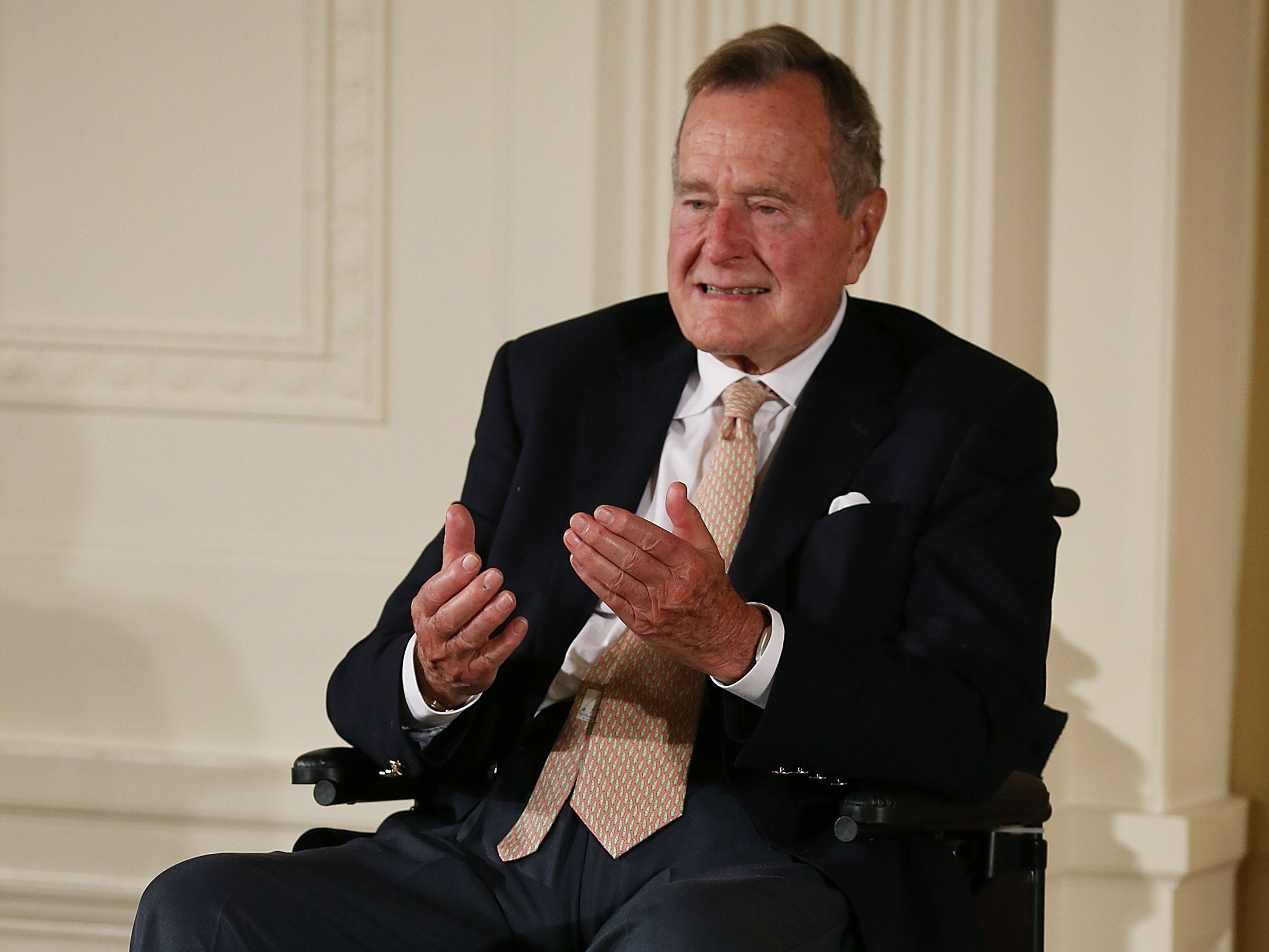 WASHINGTON, DC - JULY 15:  Former President George H. W. Bush wears red stripped socks as he sits in a wheelchair during an event in the East Room at the White House, July 15, 2013 in Washington, DC. Bush joined President Obama in hosting the event to honor the 5,000th Daily Point of Light Award winner.  (Photo by Mark Wilson/Getty Images) [Via MerlinFTP Drop]