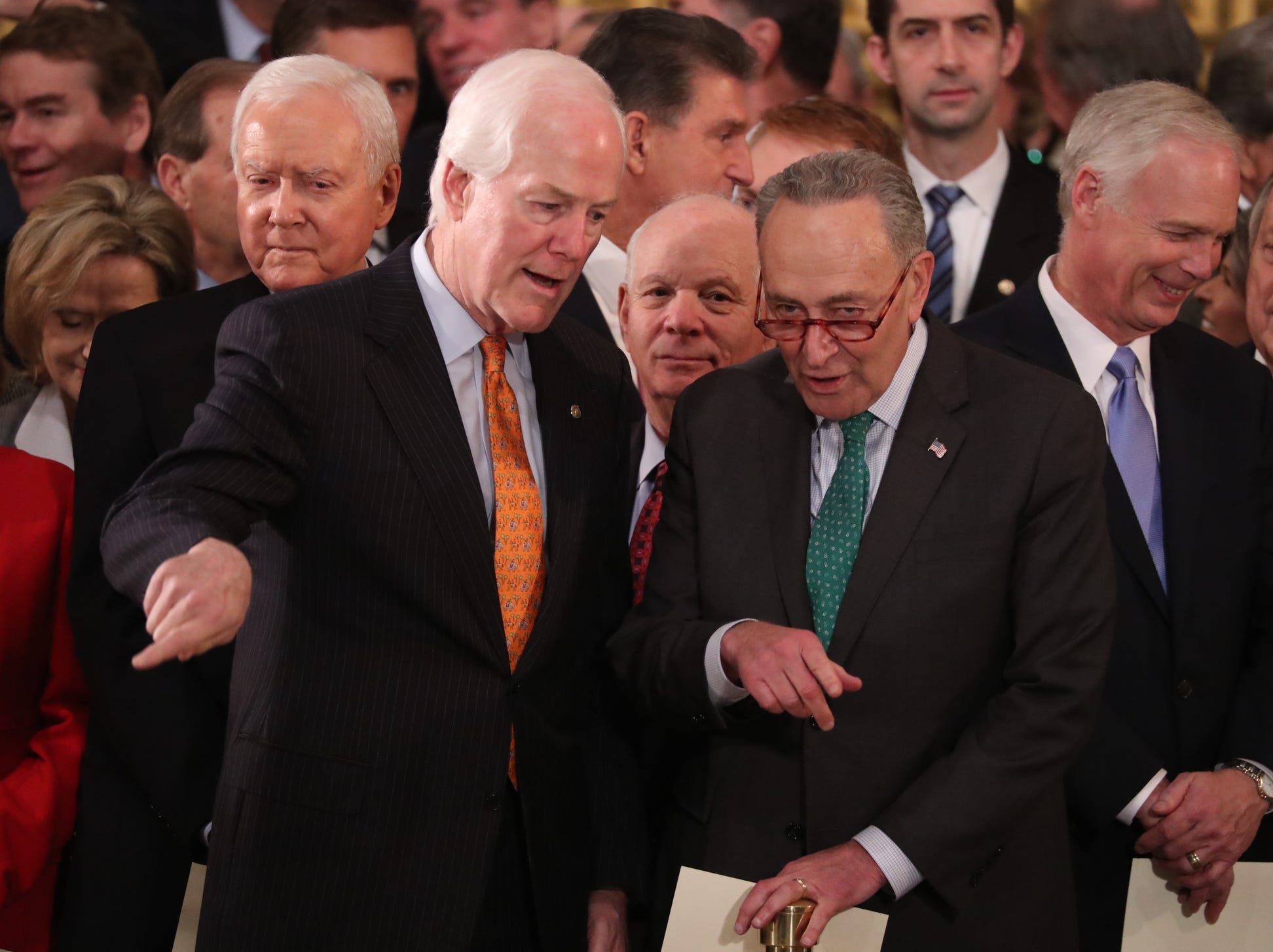 U.S. Senate Majority Whip John Cornyn and Senate Minority Leader Chuck Schumer talk while Senator Orrin Hatch (L-Rear) looks on as they attend ceremonies for the late President George H.W. Bush inside the U.S. Capitol Rotunda.  A WWII combat veteran, Bush served as a member of Congress from Texas, ambassador to the United Nations, director of the CIA, vice preside
