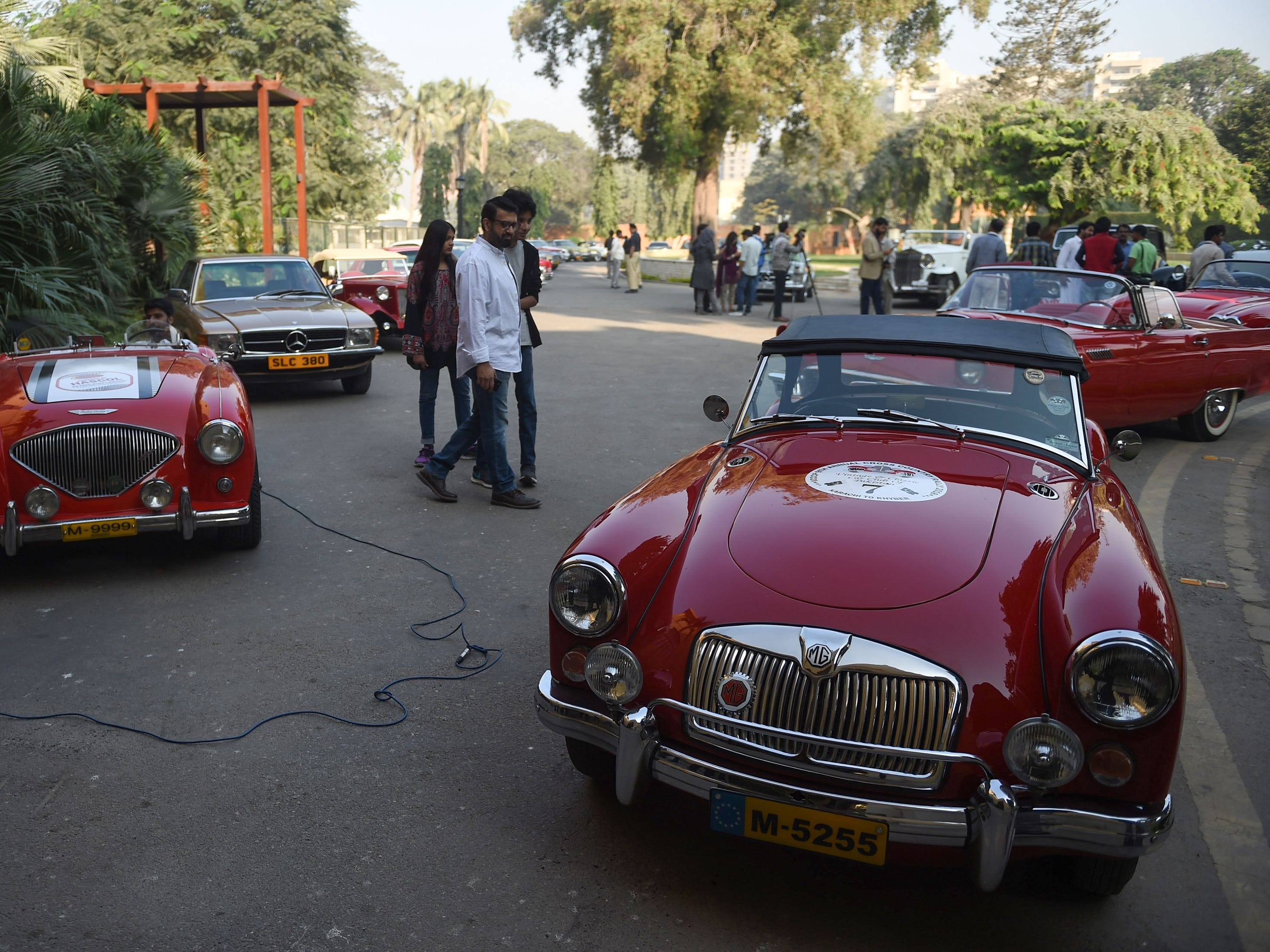 Visitors look at vintage cars during the annual ninth cross country rally organized by the Vintage and Classic Car Club of Pakistan (VCCCP) in Karachi on December 1, 2018. (Photo by RIZWAN TABASSUM / AFP)RIZWAN TABASSUM/AFP/Getty Images ORIG FILE ID: AFP_1B93X5