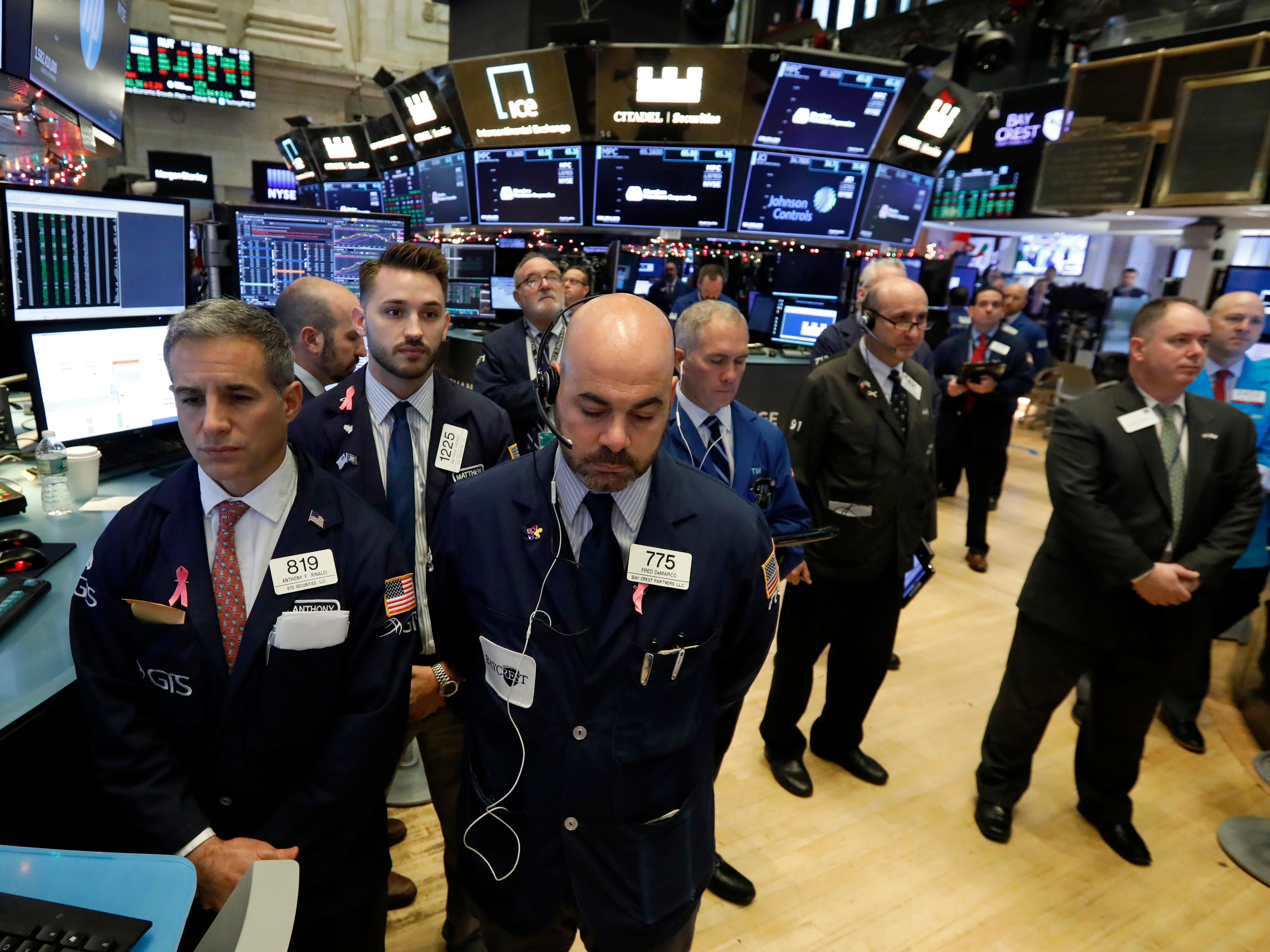 Traders on the floor of the New York Stock Exchange pause for a moment of silence to honor former President George H.W. Bush, Monday, Dec. 3, 2018.