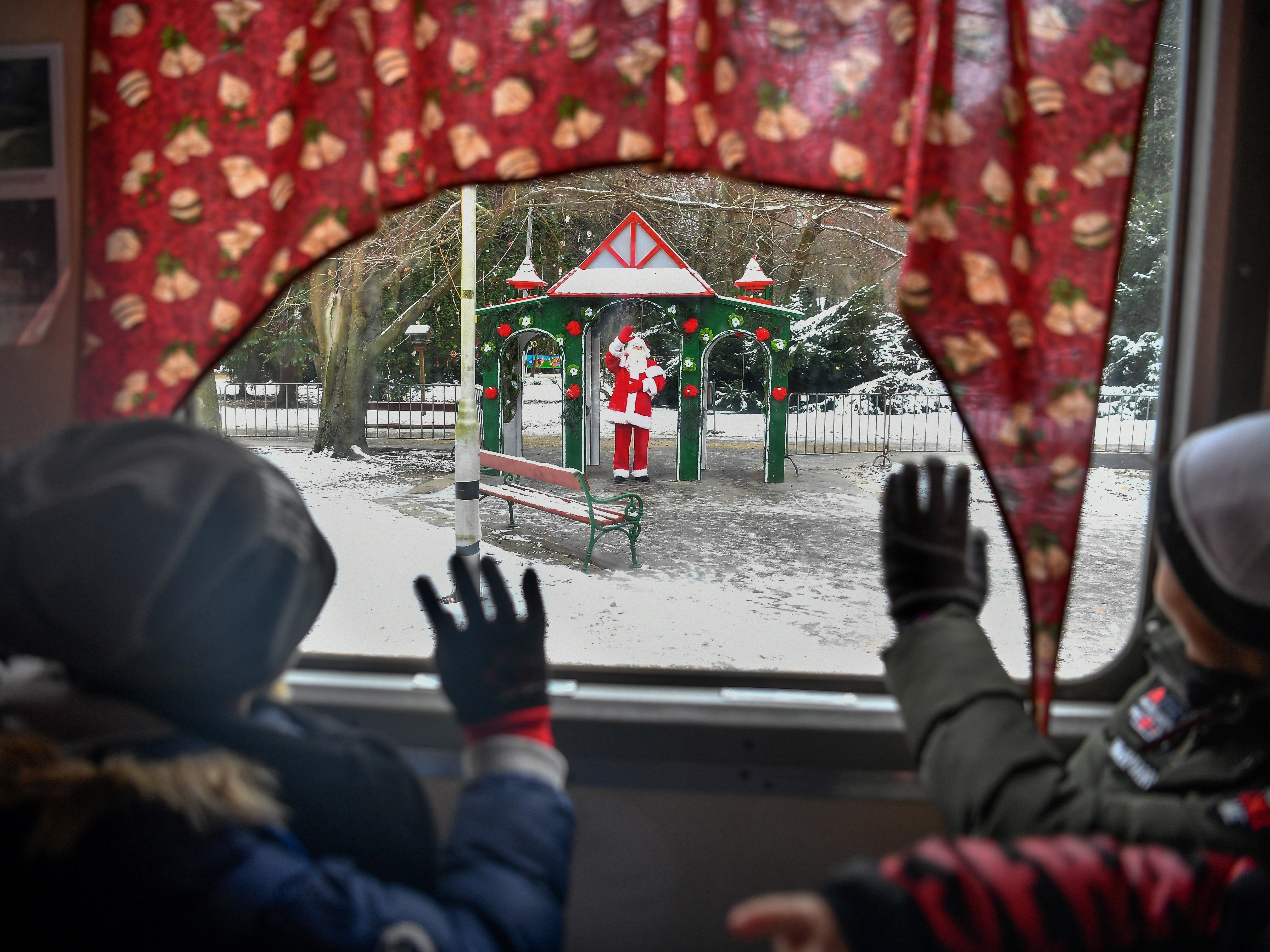 Santa Claus waves to children upon their arrival with the Diosgyor Santa Claus Train in the railway station in Lillafured, Hungary, Nov. 29, 2018.