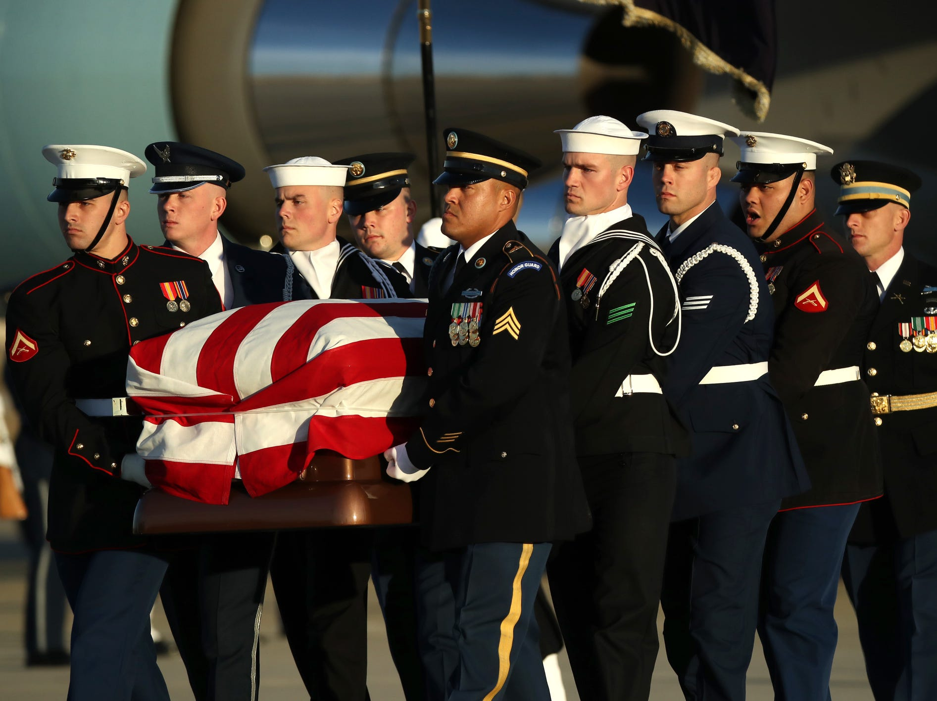 Service members carry the casket of the remains of former U.S. President George H.W. Bush is carried out of the U.S. Air Force 747, being called 'Special Mission 41, Monday.