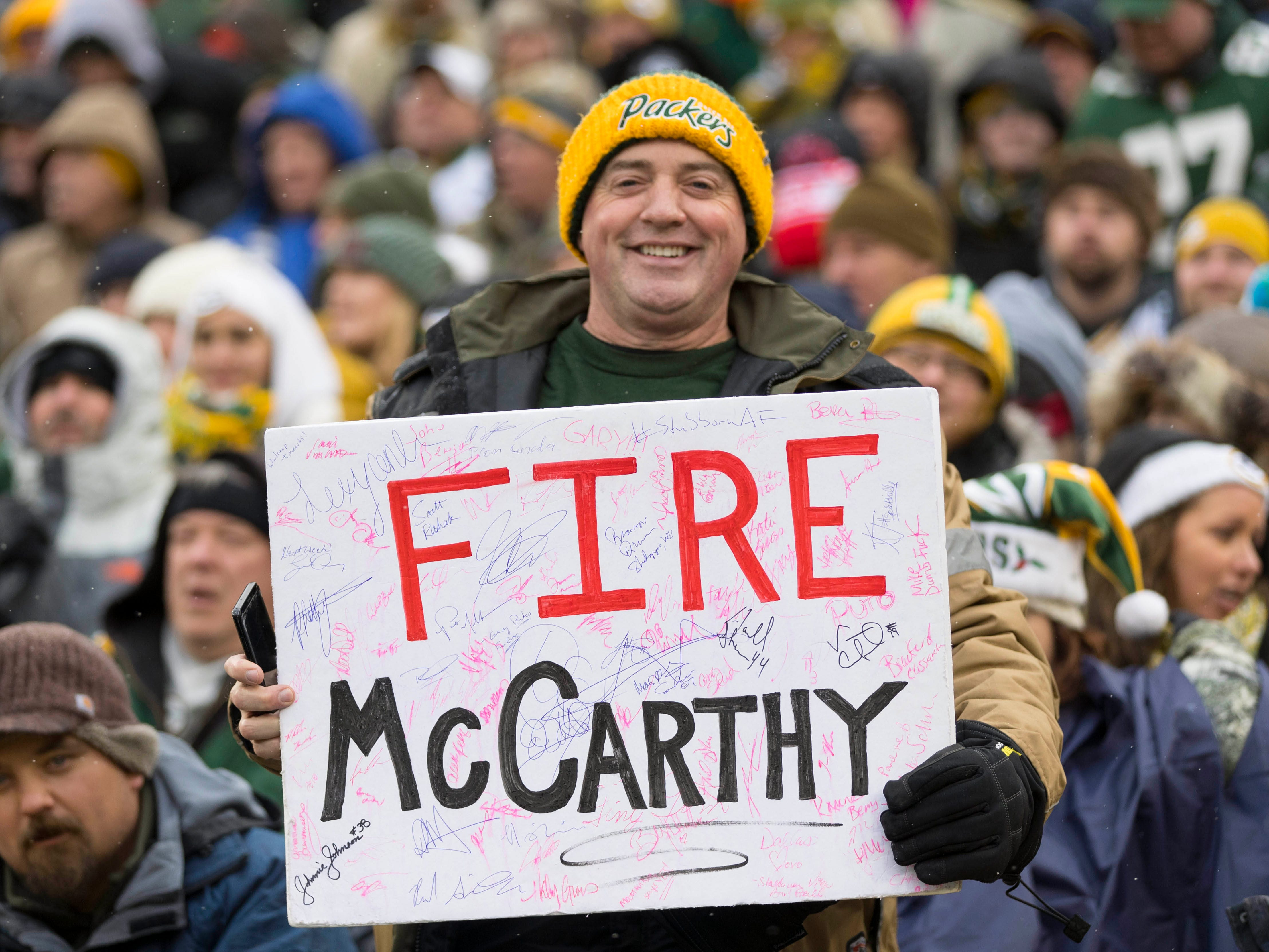 A Green Bay Packers fan holds up a sign encouraging the firing of Mike McCarthy during the second quarter against the Arizona Cardinals at Lambeau Field.