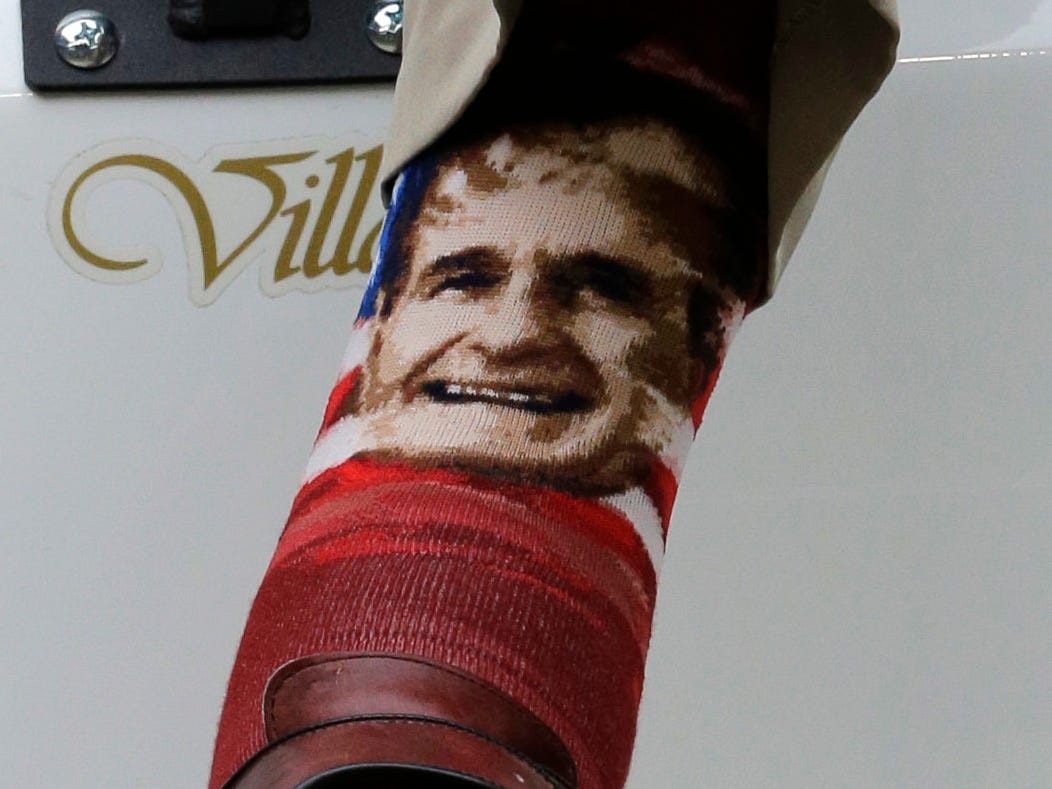 Former President George H.W. Bush wears socks with his image as he sits in a cart on the sidelines before an NFL football game between the New England Patriots and Houston Texans on Dec. 1, 2013, in Houston. (AP Photo/David J. Phillip, File) ORG XMIT: NYAJ105