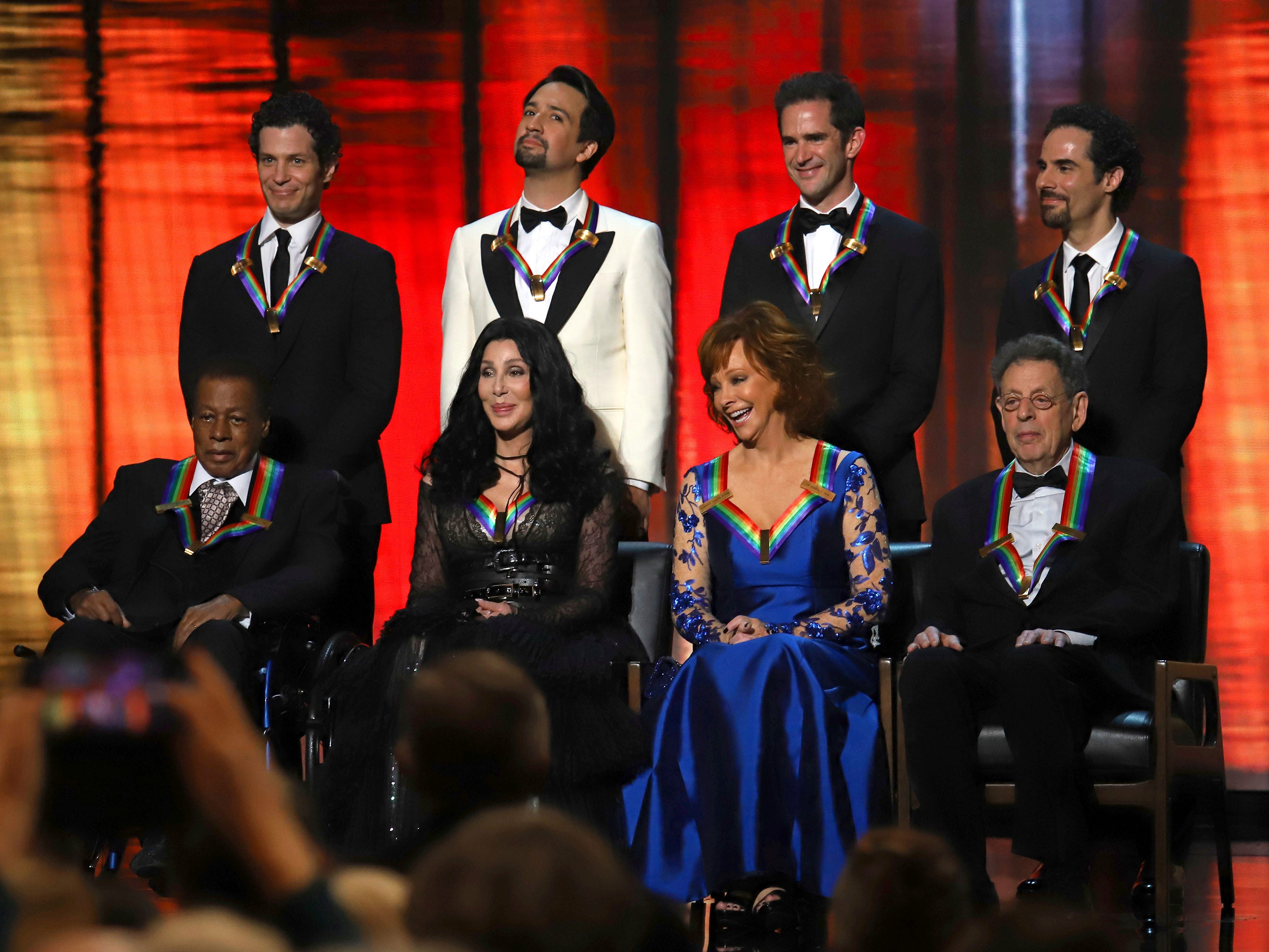 "2018 Kennedy Center honorees, front row from left, Wayne Shorter, Cher, Reba McEntire and Philip Glass; while back row from left, the co-creators of ""Hamilton,"" Thomas Kail, Lin-Manuel Miranda, Andy Blankenbuehler and Alex Lacamoire appear on stage during the 41st Annual Kennedy Center Honors at The Kennedy Center, Sunday, Dec. 2, 2018, in Washington. (Photo by Greg Allen/Invision/AP) ORG XMIT: NYGA103"