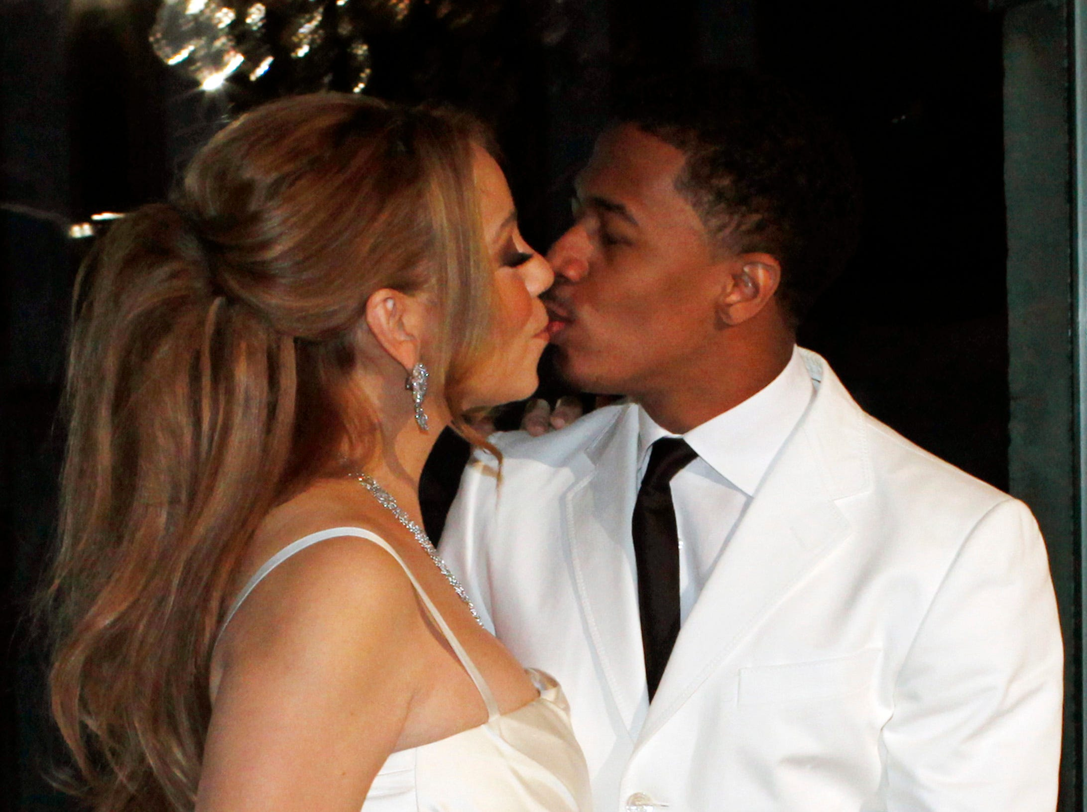 ORG XMIT: XTC101 U.S singer Mariah Carey, left, kisses her husband Nick Cannon as they pose in Paris, for the renewal of their wedding vows, Friday, April 27, 2012. (AP Photo/Thibault Camus)