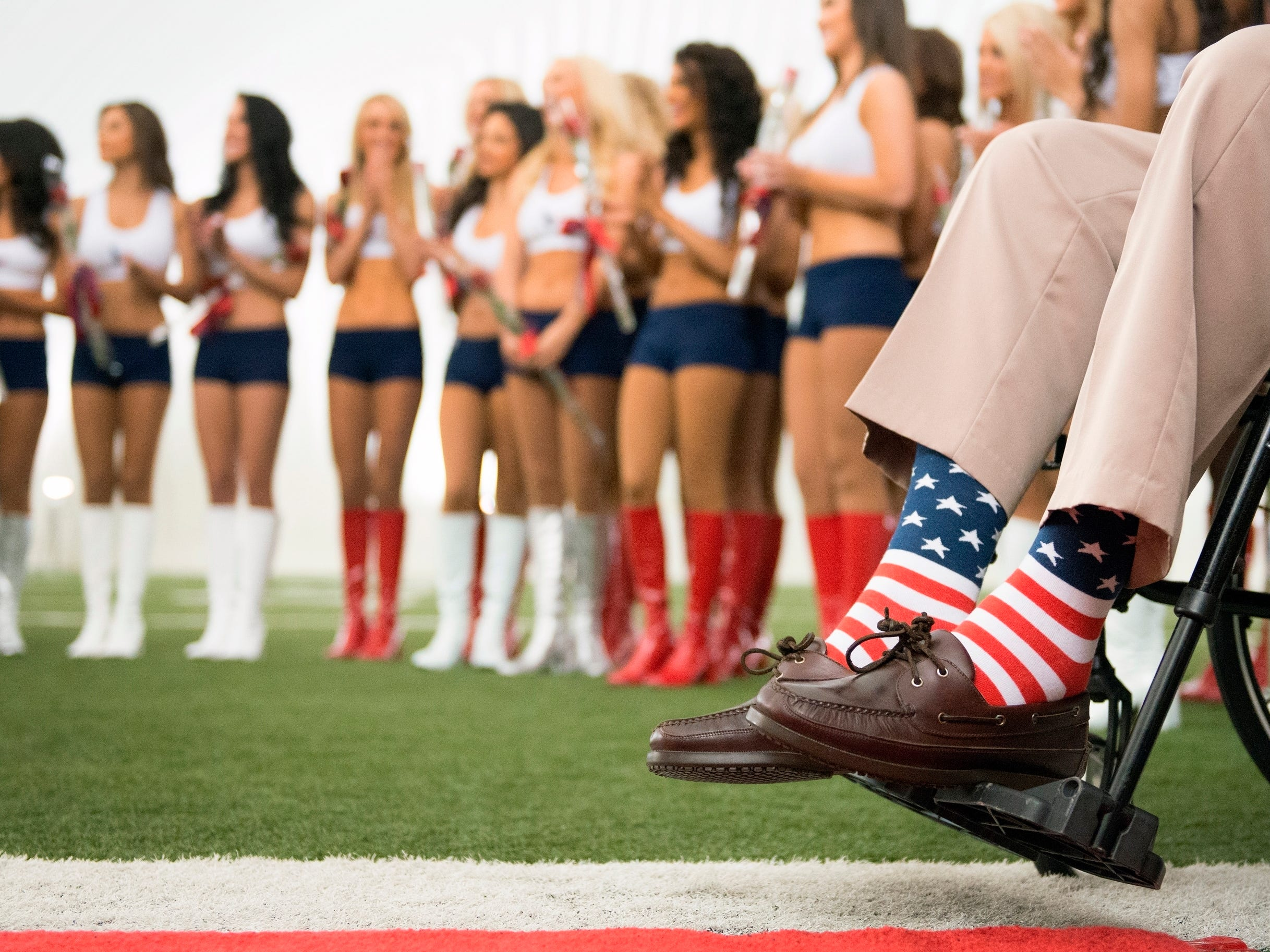 Former President George H.W. Bush wears American flag socks as he presents roses to the new Houston Texans cheerleaders during a ceremony introducing the new squad at the team's NFL football training facility in Houston on April 17, 2013. Bush often sported bright socks, sometimes with loud, unusual patterns. He died Friday, Nov. 30, 2018, in Houston at age 94. (Smiley N. Pool/Houston Chronicle via AP, File) ORG XMIT: NYAJ101