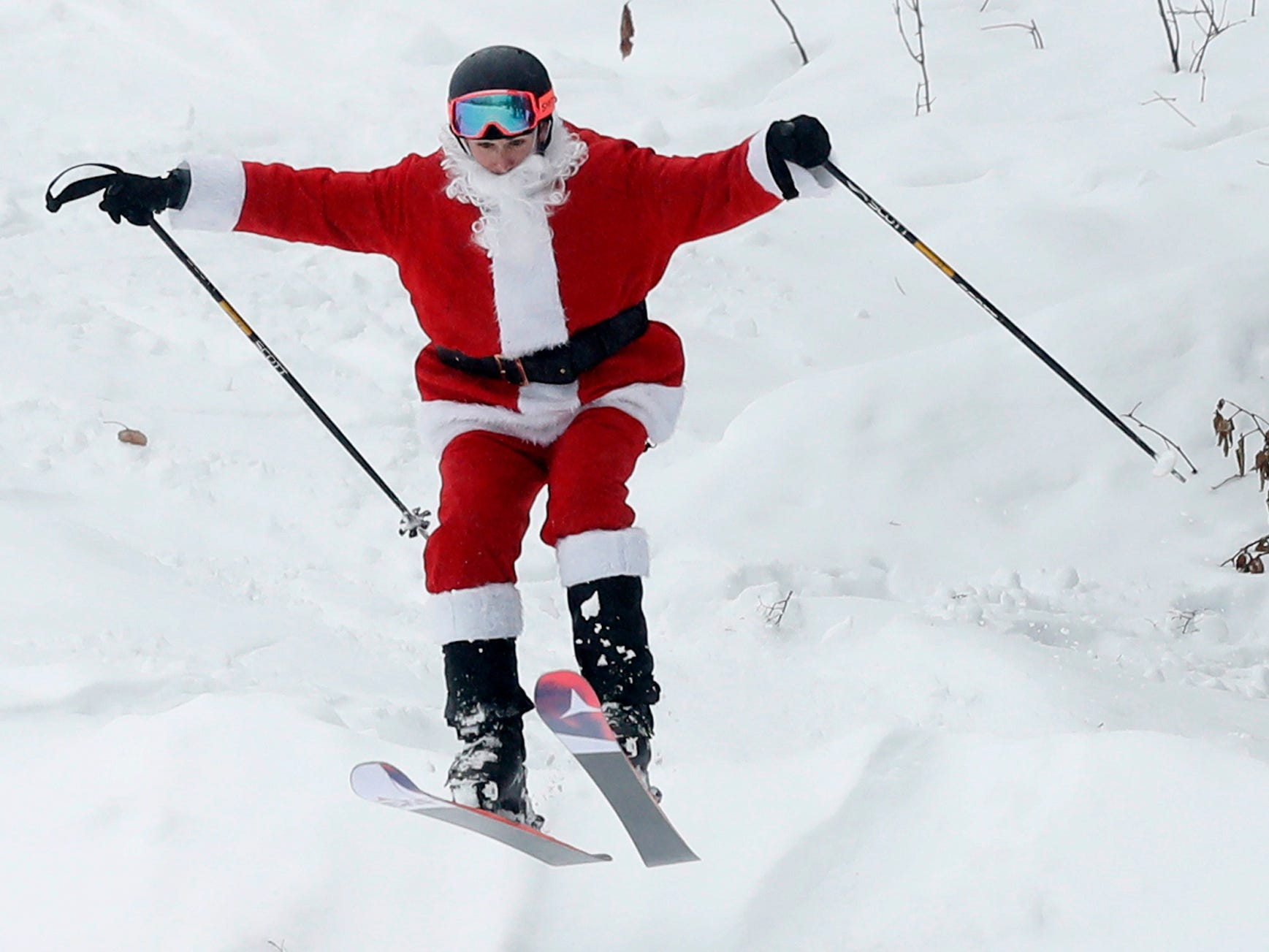 A skier dressed as Santa Claus takes flight during the annual Santa Sunday event, Sunday, Dec. 2, 2018, in Newry, Maine. The red-suited lookalikes aim to put a smile on peopleÕs faces while raising money for charity.