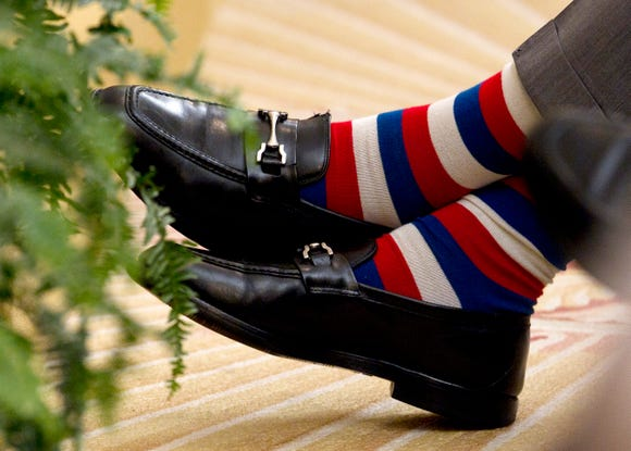 Former President George H.W. Bush crosses his red, white and blue socked feet during a ceremony to unveil the portraits of his son, former President George W. Bush, and former first lady Laura Bush on May 31, 2012, at the White House in Washington.