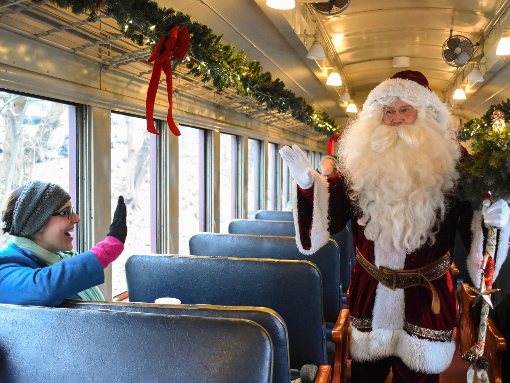 Carrie Nedick, of Fogelsville, Pa., waves to Santa while he walks through the train car after boarding the Santa Claus Steam Train Ride at the Minersville Train Station in Minersville, Pa., on Saturday, Dec. 1, 2018.
