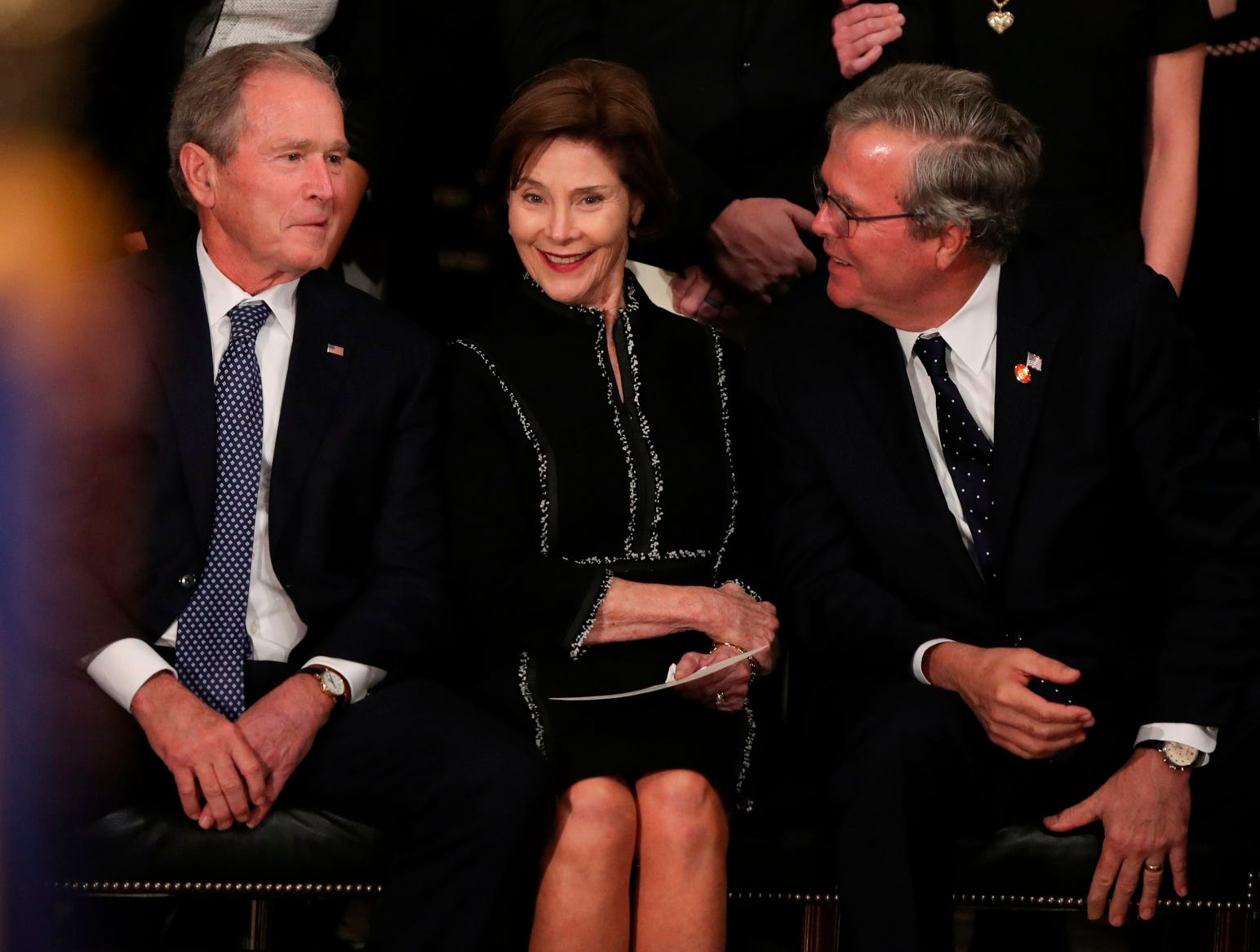 Former president George W. Bush, left, former first lady Laura Bush, and former Florida Governor Jeb Bush share a moment as the late former President George H.W. Bush lies in state inside the Rotunda of the US Capitol.