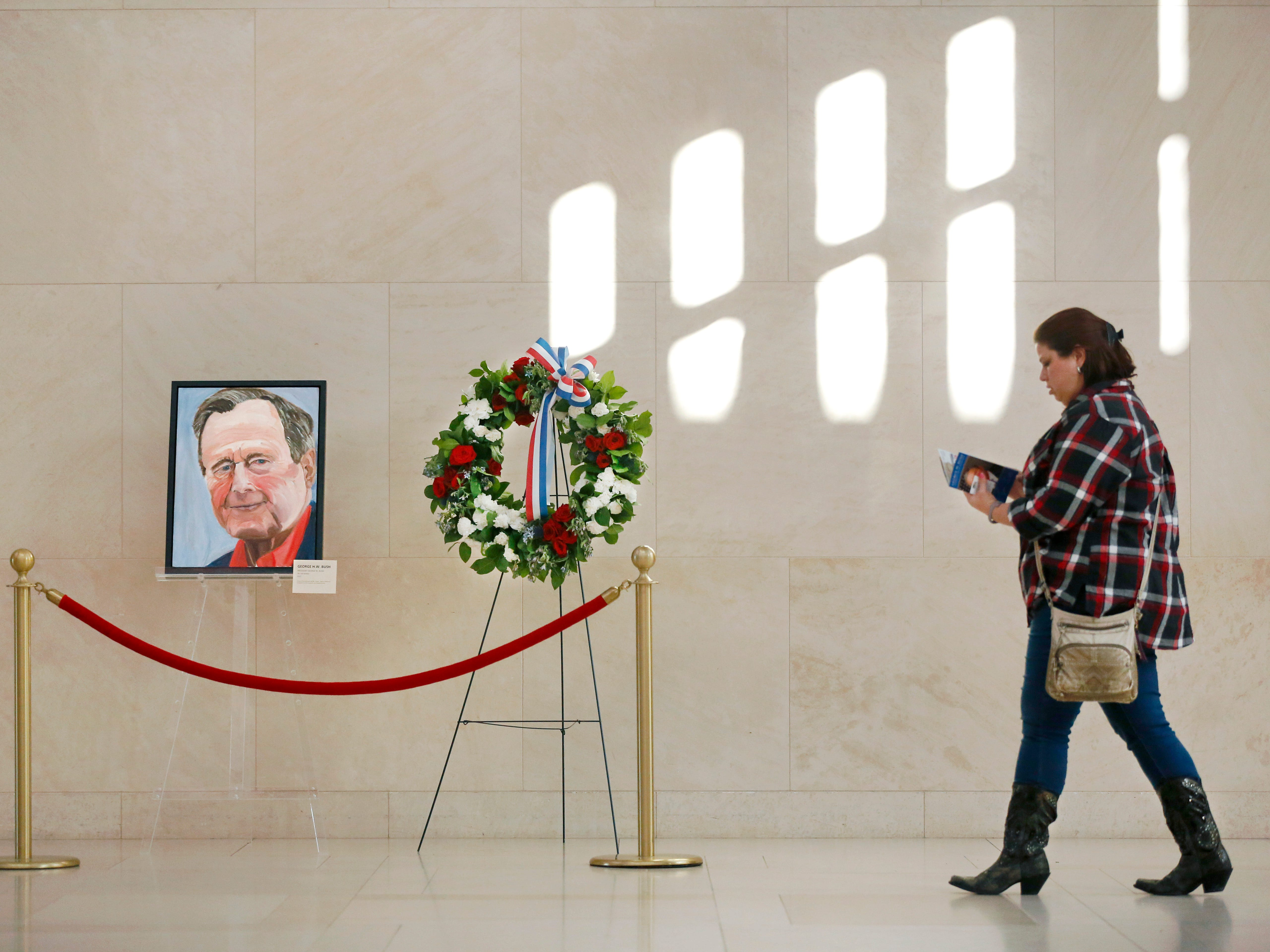 A guest to the George W. Bush Presidential Library and Museum in University Park, Texas passes by a painted portrait of Bush's father, the late 41st President George H.W. Bush -- painted by former Pres. George W. Bush -- and a memorial wreath, Sunday, Dec. 2, 2018.