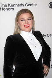 Kelly Clarkson poses on the red carpet before paying tribute to Reba McEntire.