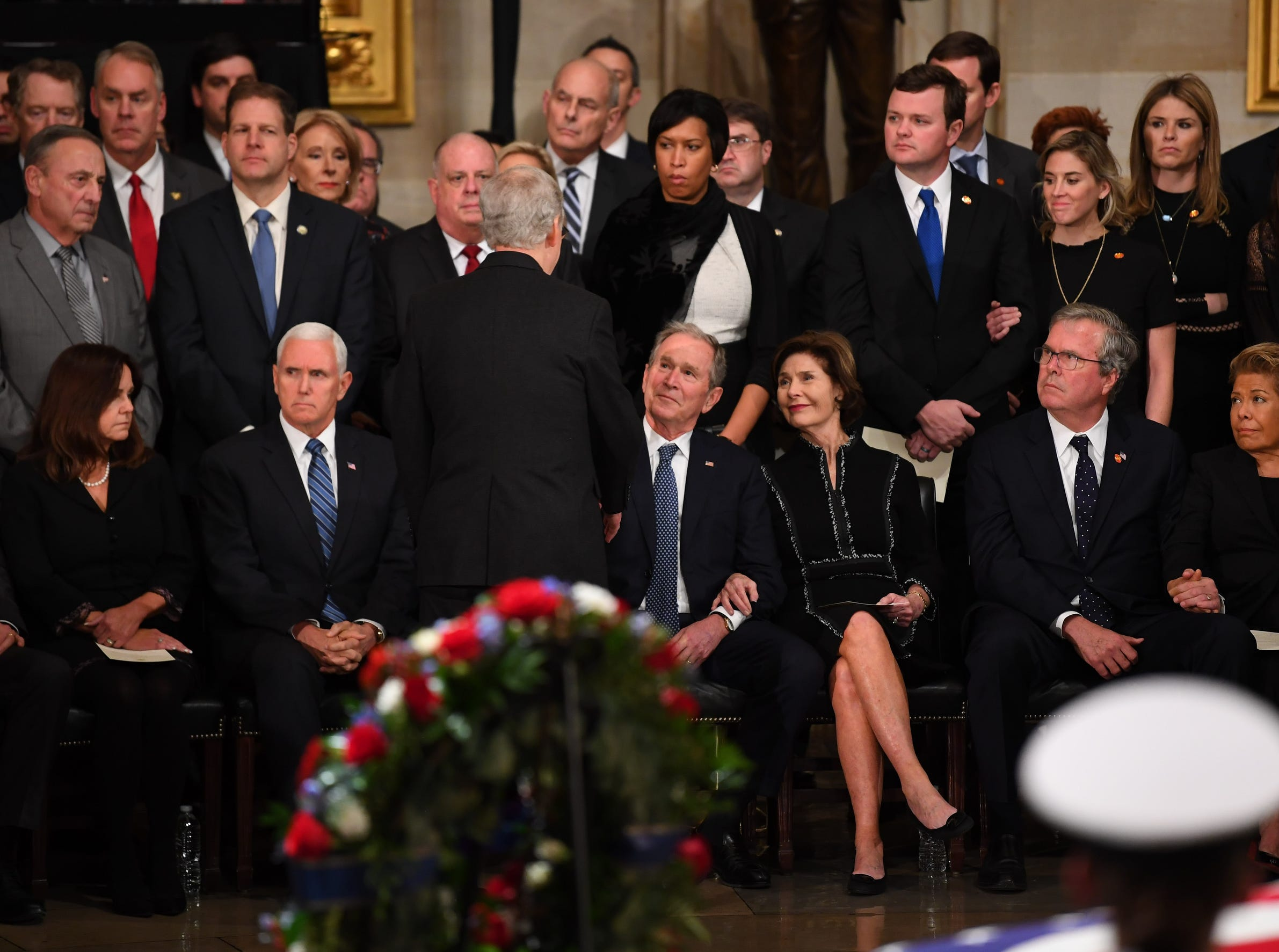 Speaker McConnell greets President George W. Bush as family members and others look on. at the Capitol Rotunda.