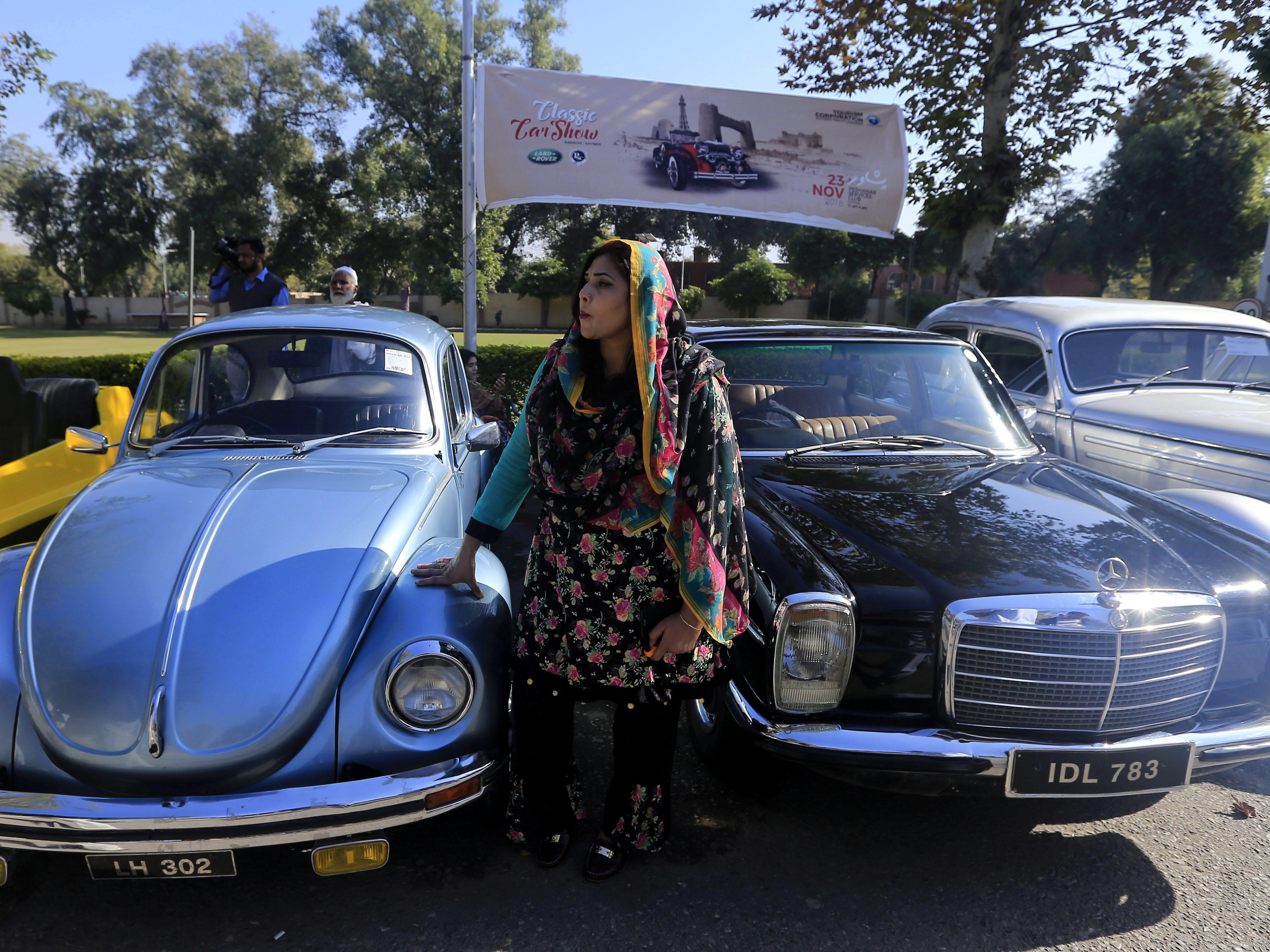 epa07185124 A Pakistani women stands near vintage cars on display during a show organized by the Vintage and Classic Car Club of Pakistan in Peshawar, Pakistan, 23 November 2018. More than 60 vintage and classic cars were on display from all across Pakistan, some coming all the way from Karachi and heading on to Khyber.  EPA-EFE/BILAWAL ARBAB ORG XMIT: PSH01