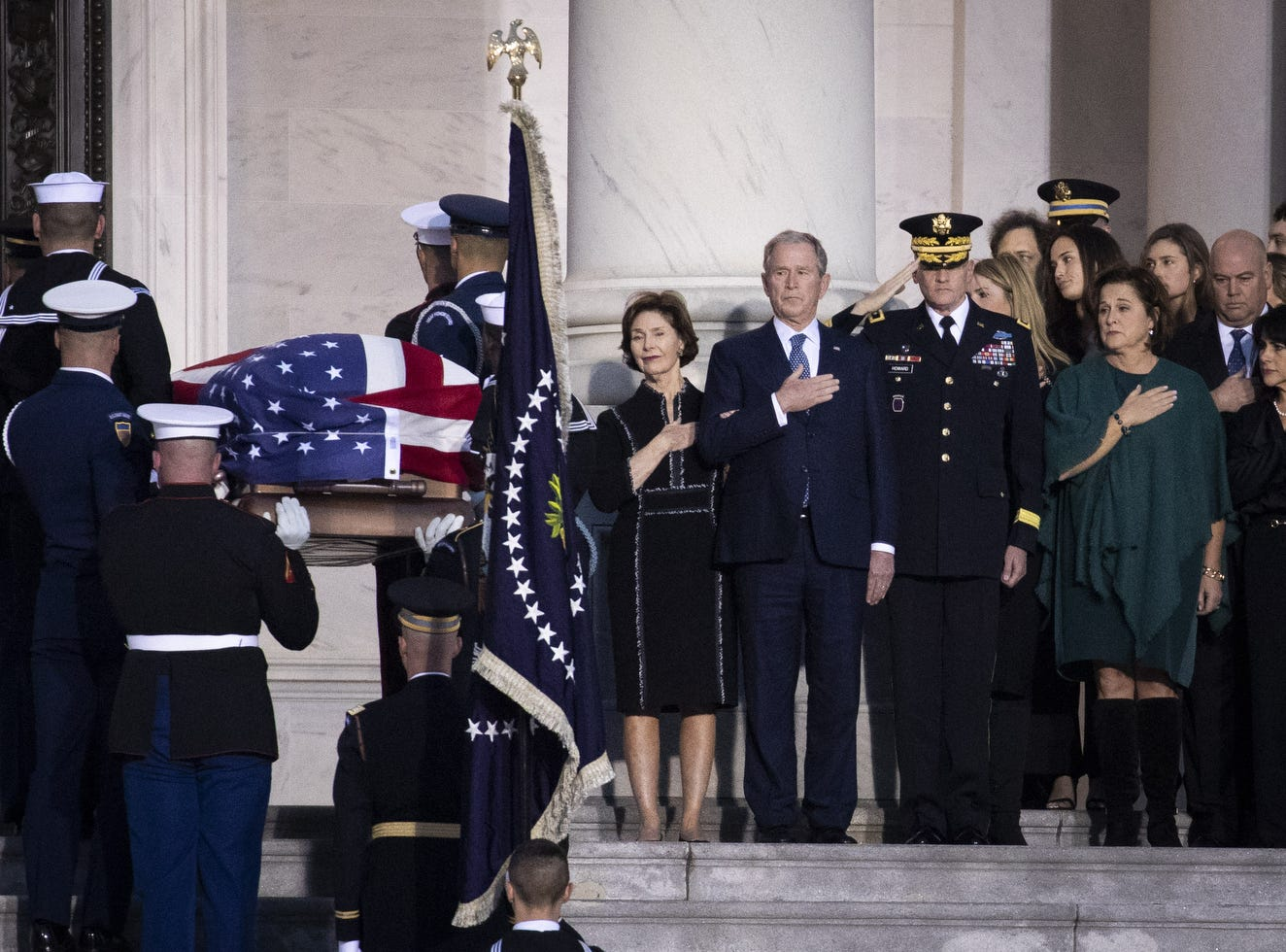 Former first lady Laura Bush and former president George W. Bush look on as the casket of the late former President George H.W. Bush arrives at the U.S. Capitol, Dec. 3, 2018.  A state funeral for Bush will be held in Washington over the next three days, beginning with him lying in state in the U.S. Capitol Rotunda until Wednesday morning.