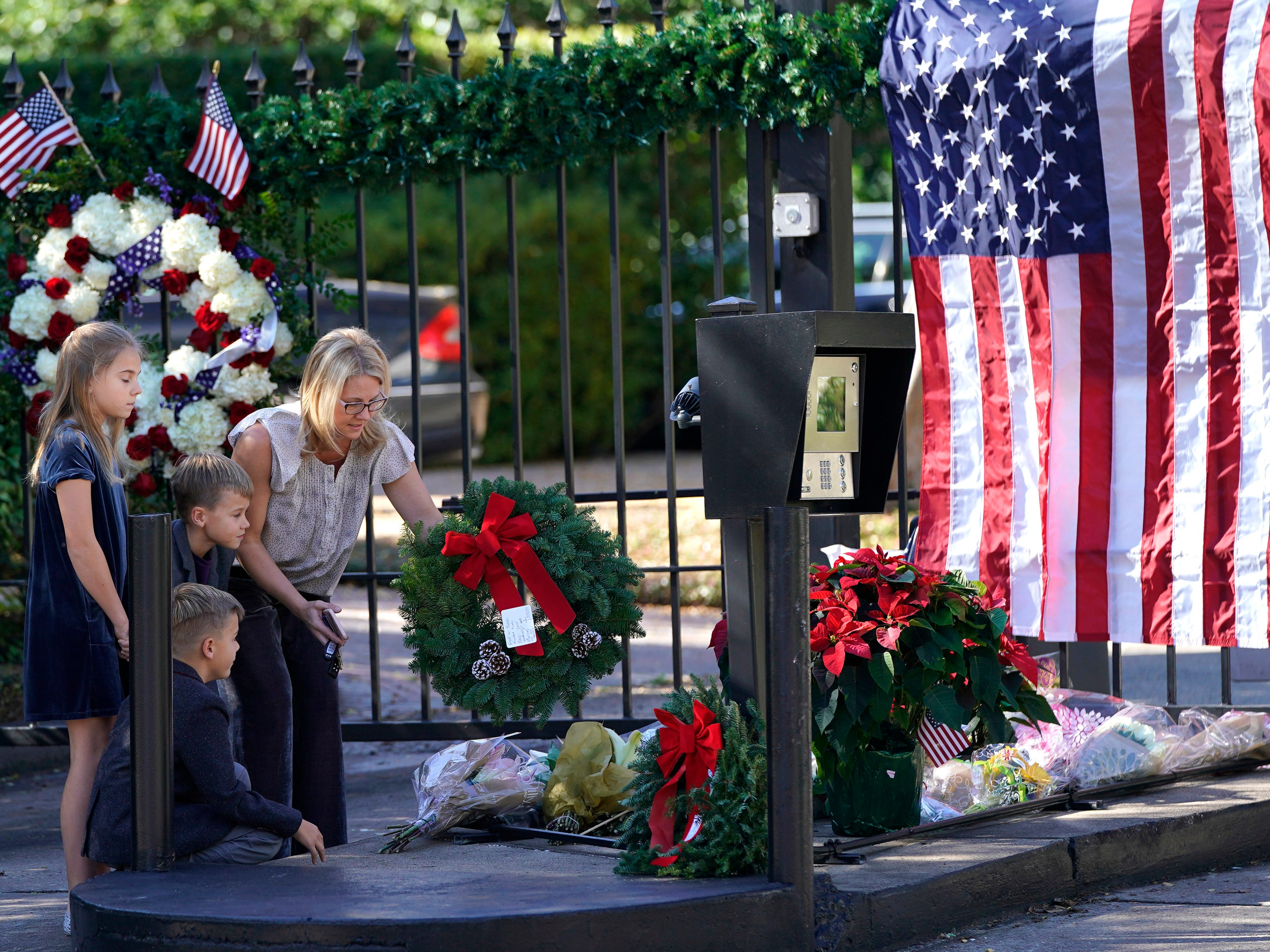 Tiffany Utterson, right, and her children, from left to right, Ella, 11, Ian, 10 and Owen, 8, place a wreath outside the gated community entrance to the home of George H.W. Bush Sunday, Dec. 2, 2018, in Houston.