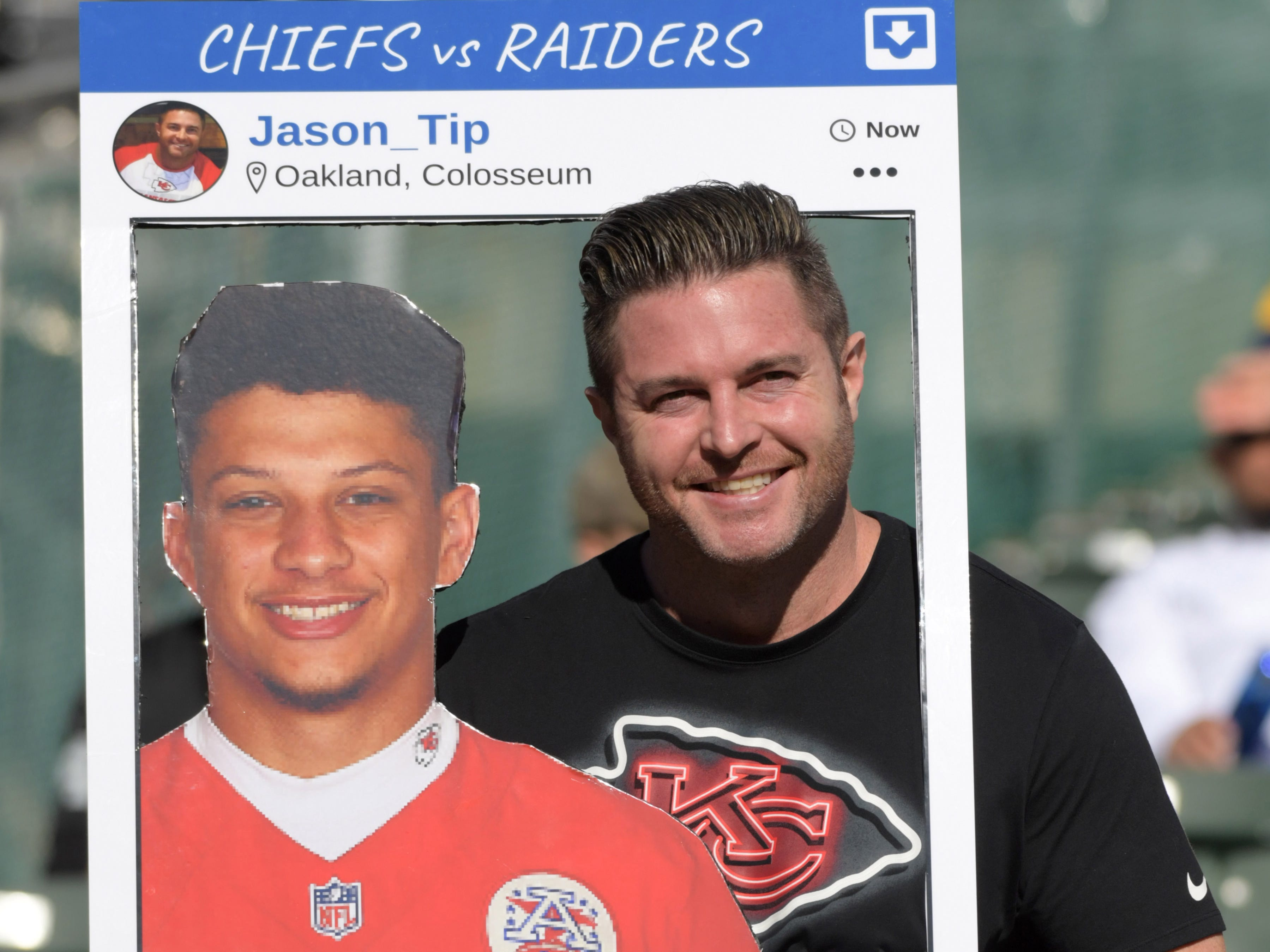 A fan of the Kansas City Chiefs poses an Instagram frame with cutout of quarterback Patrick Mahomes during the game against the Oakland Raiders at Oakland-Alameda County Coliseum.