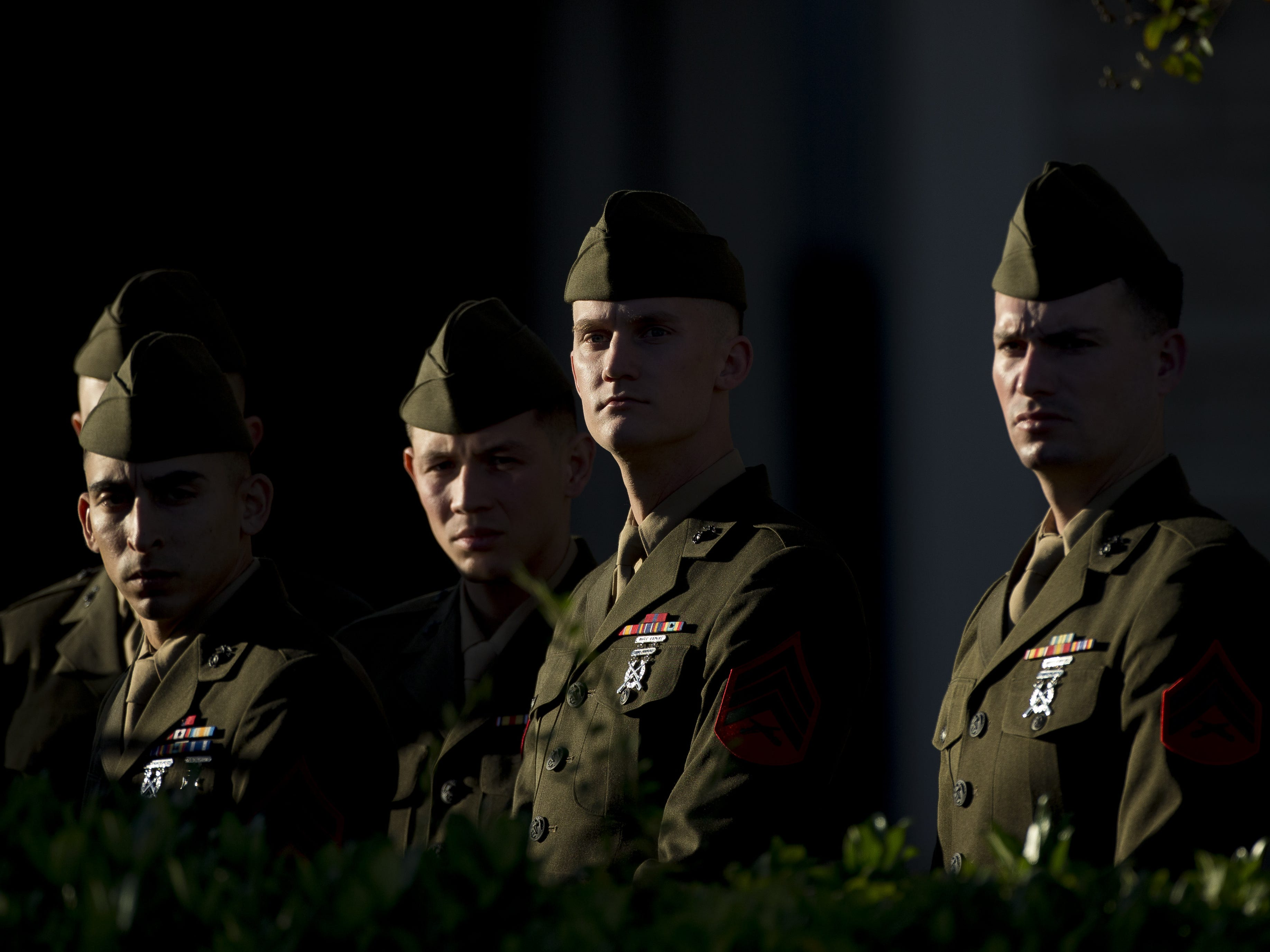 Members of the U.S. Marine Corps in their dress greens stand outside where the remains of former President George H.W. Bush are kept before the first departure ceremony at George H. Lewis and Sons Funeral Home on Dec. 3, 2018, in Houston