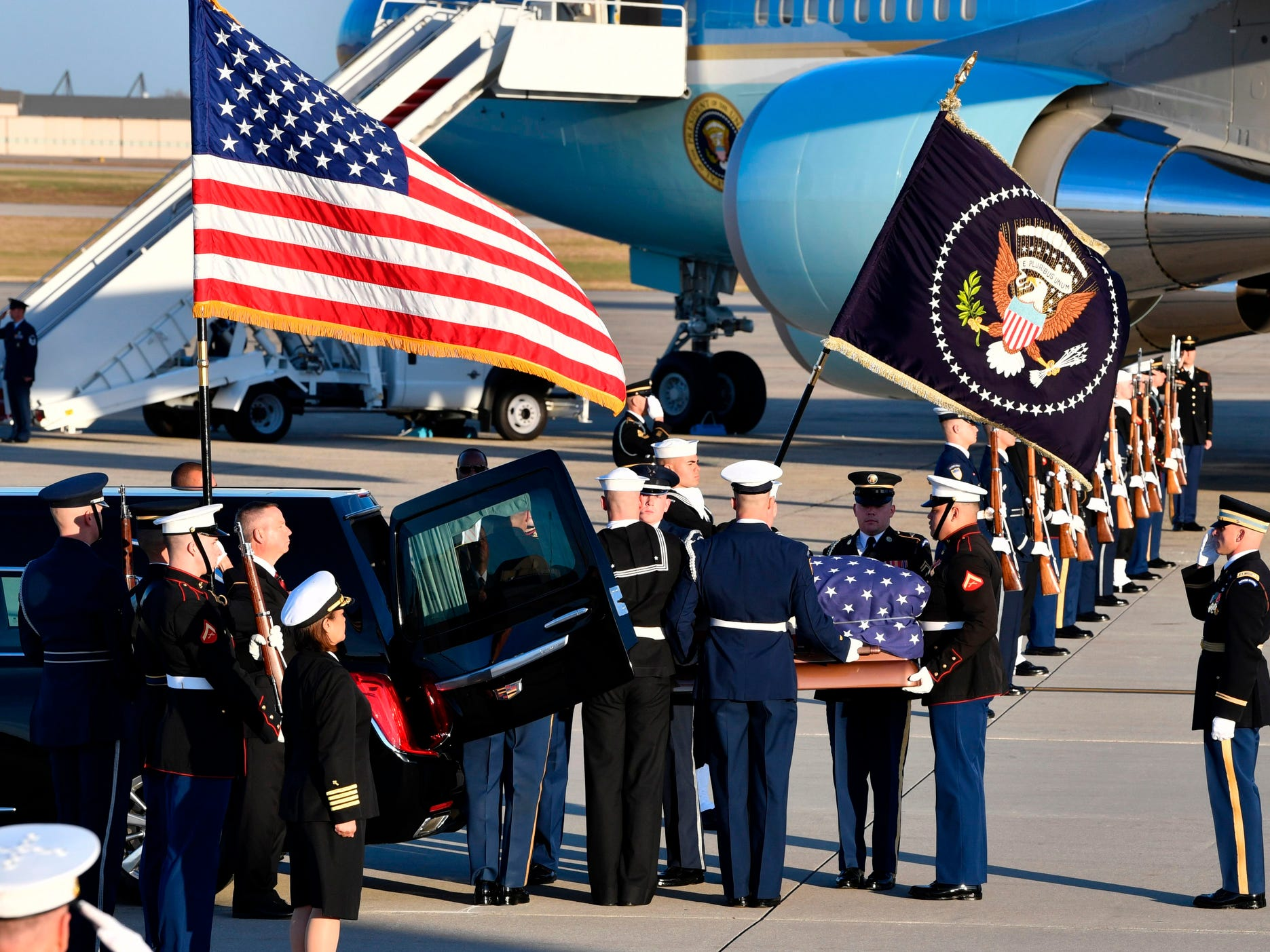 The flag-draped casket of former President George H.W. Bush is carried by a joint services military honor guard to the hearse at Joint Base Andrews.