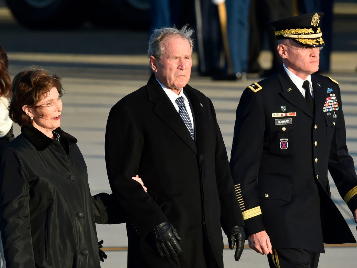 Former US President George W. Bush, center, and former First Lady Laura Bush walk from Special Air Mission 41, the plane that carried his father, former US President George H.W. Bush, to Washington ,DC Joint Base Andrews, MD, on Dec. 3, 2018.