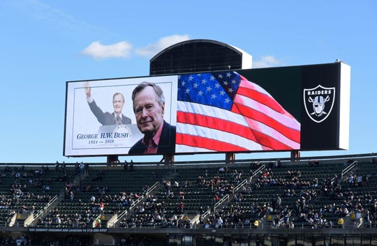A moment of silence is observed in the memory of former President George H.W. Bush during the NFL game between the Kansas City Chiefs and the Oakland Raiders in Oakland, Calif., Dec. 2, 2018.
