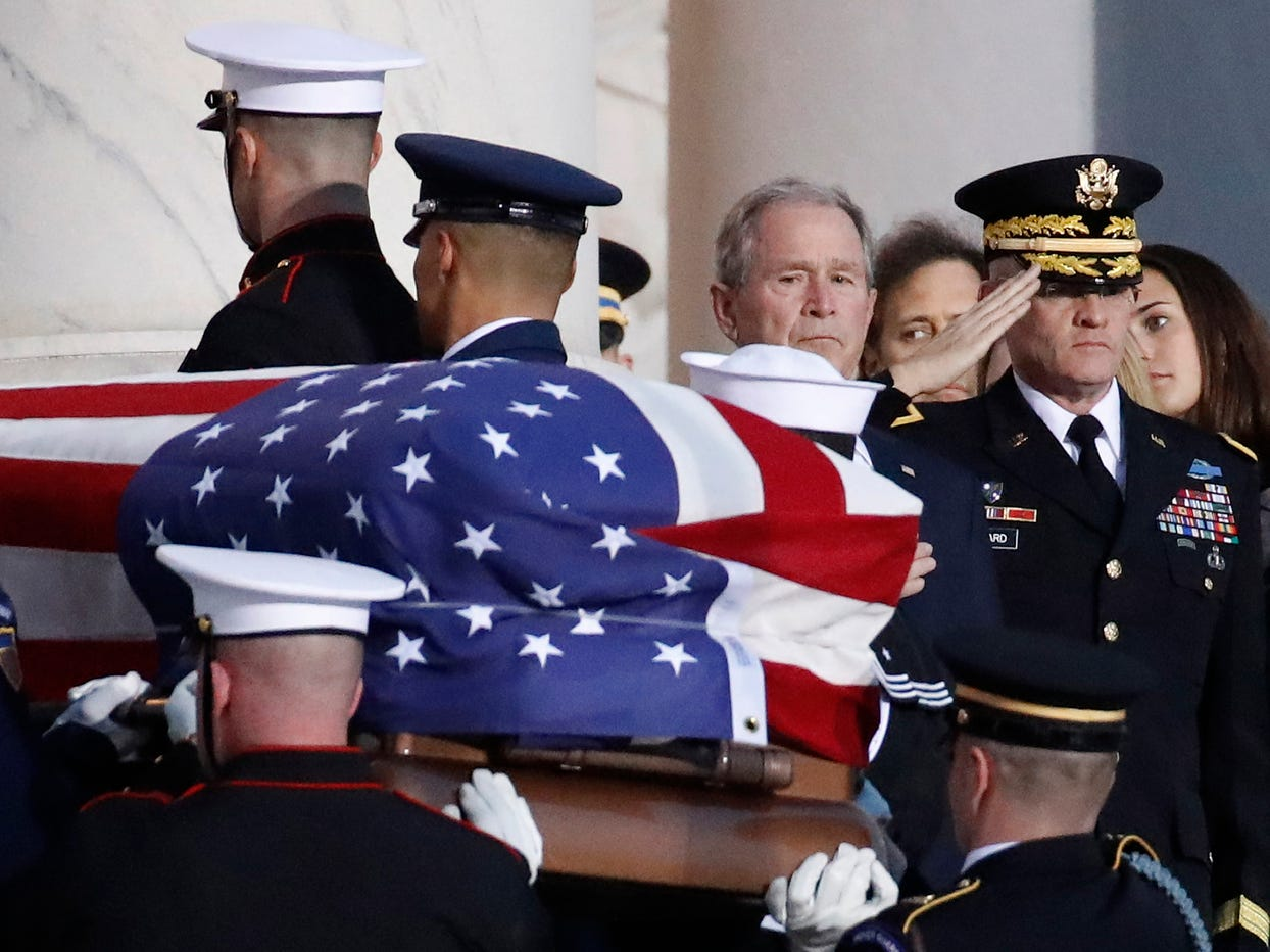 Former President George W. Bush watches as the flag-draped casket of his father, former President George H.W. Bush is carried by a joint services military honor guard to lie in state in the rotunda of the US Capitol, Monday.