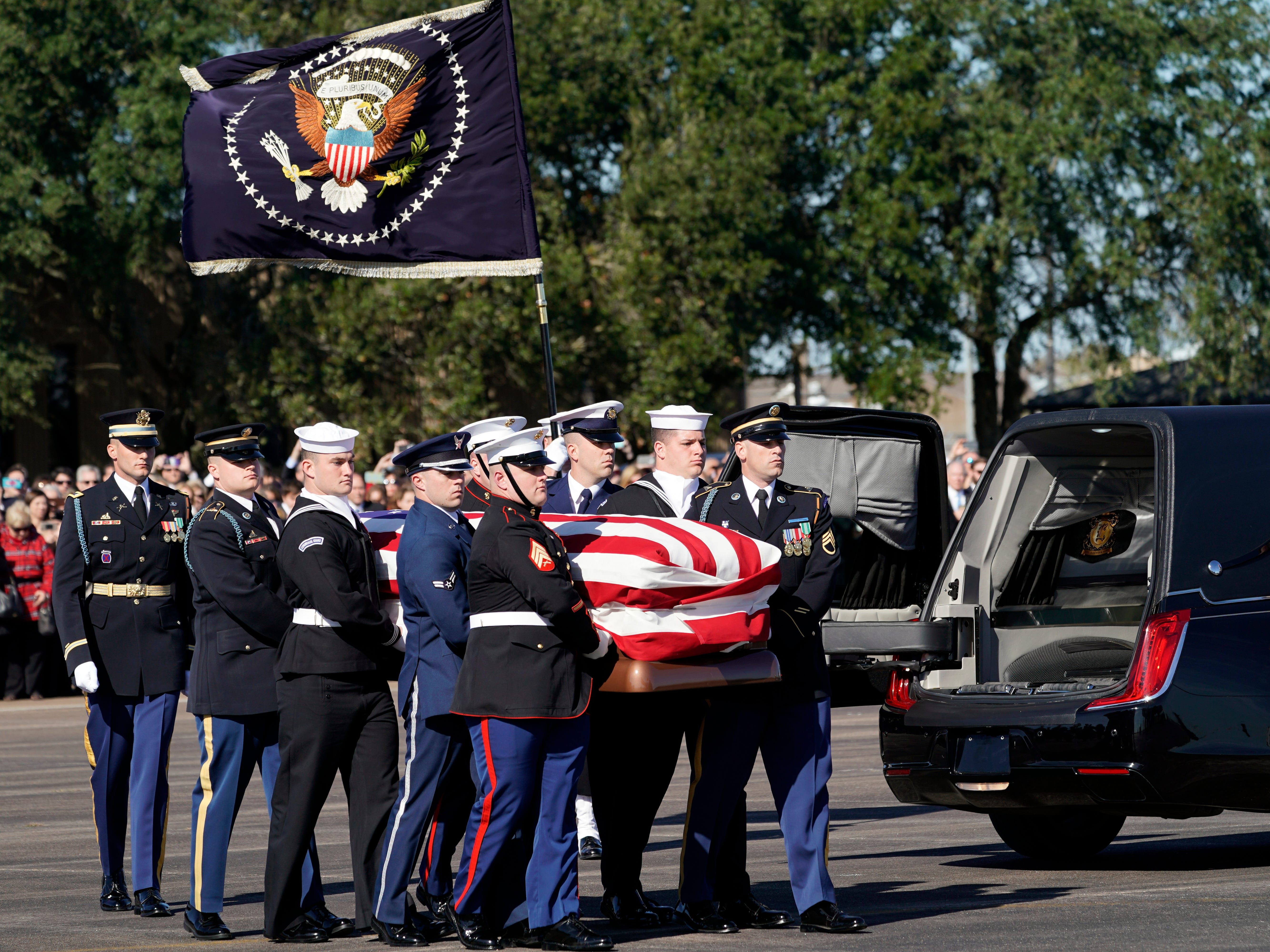 Joint services military honor guard carry the flag-draped casket of the remains of former President George H.W. Bush during a departure ceremony to Washington at Ellington Field on Dec. 3, 2018 in Houston.
