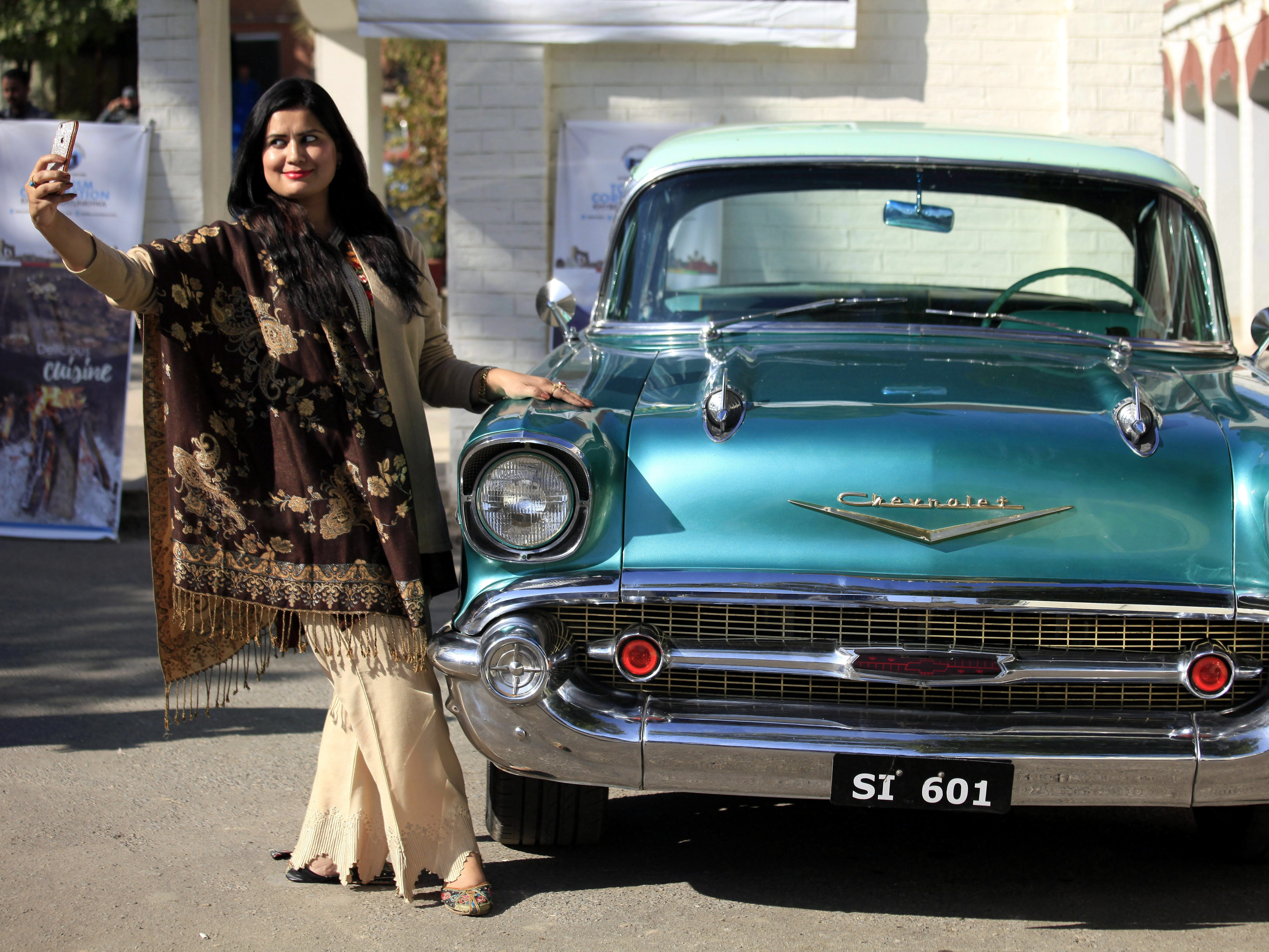epa07185125 A Pakistani girl takes a selfie next to a vintage Chevrolet '57 during a show organized by the Vintage and Classic Car Club of Pakistan in Peshawar, Pakistan, 23 November 2018. More than 60 vintage and classic cars were on display from all across Pakistan, some coming all the way from Karachi and heading on to Khyber.  EPA-EFE/BILAWAL ARBAB ORG XMIT: PSH01